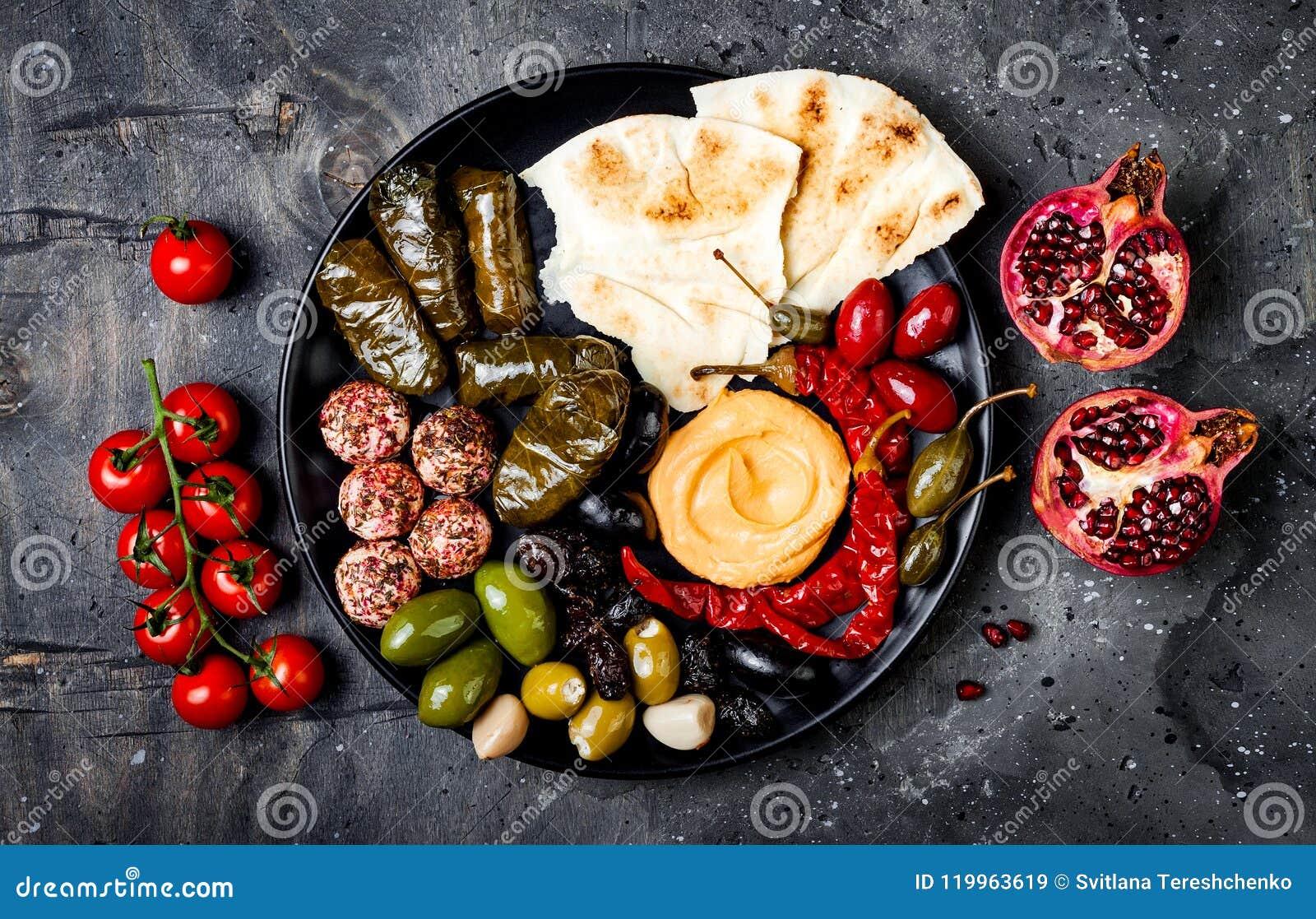 Arabische traditionele keuken De mezeschotel van het Middenoosten met pitabroodje, olijven, hummus, vulde dolma, labneh kaasballe