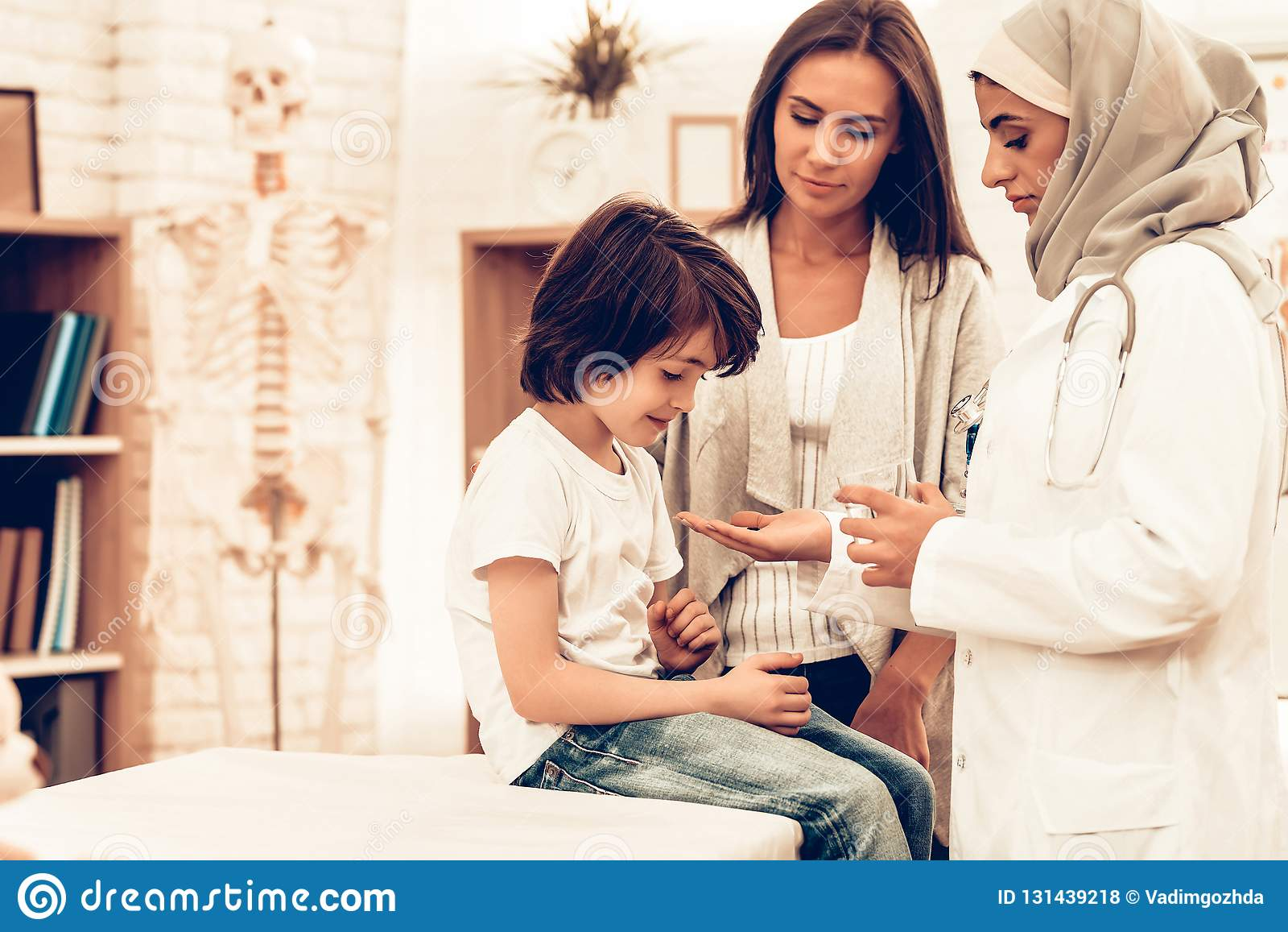 Arabisk doktor Give Medicine till liggande säng för sjuk pojke