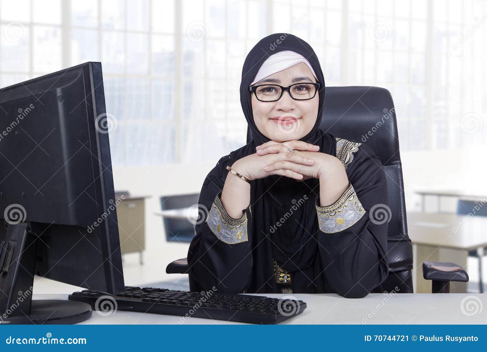 Arabisk kvinna med sjaletten som i regeringsställning ler