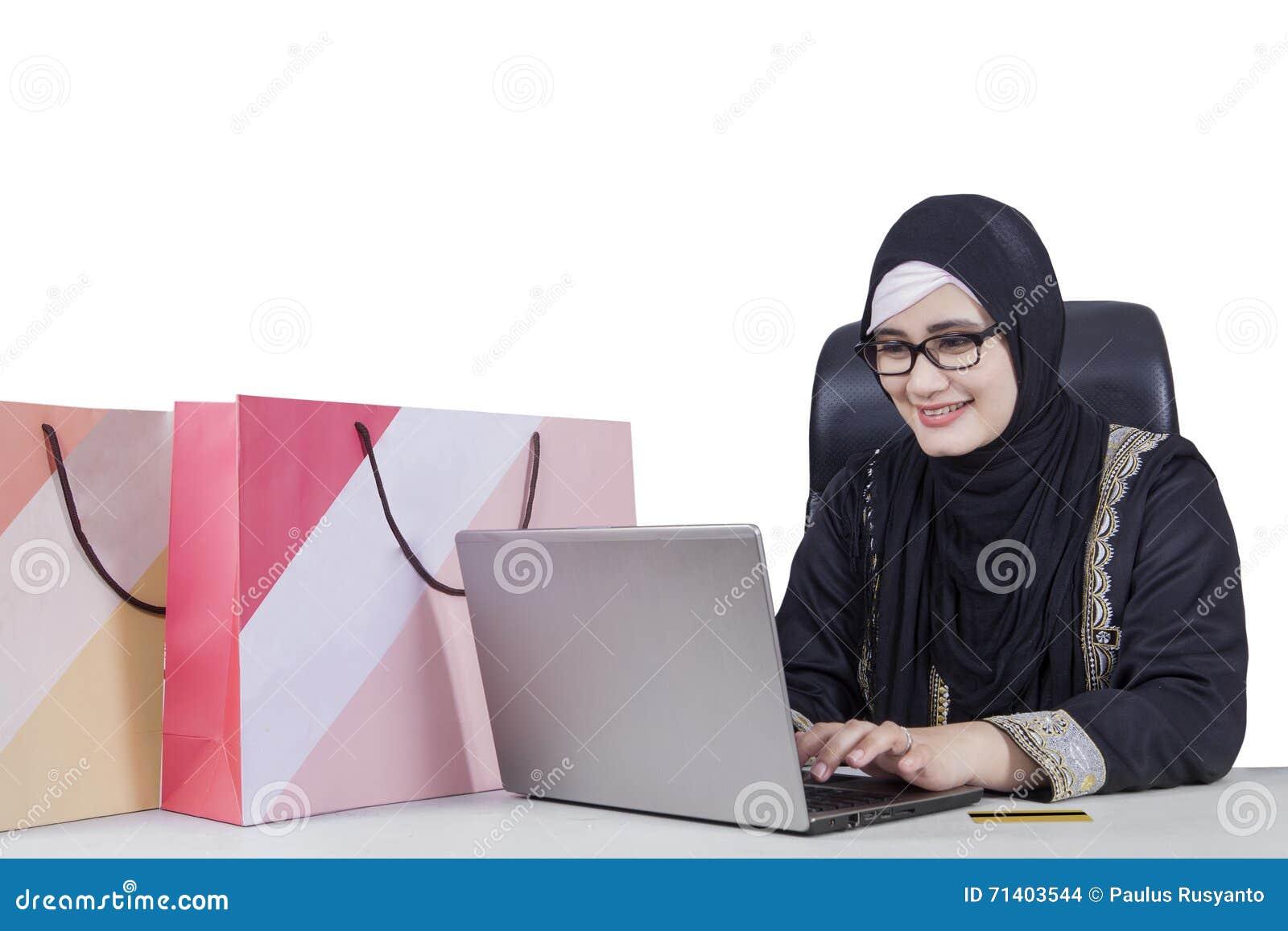 Arabisk kvinna som använder bärbara datorn för att shoppa direktanslutet