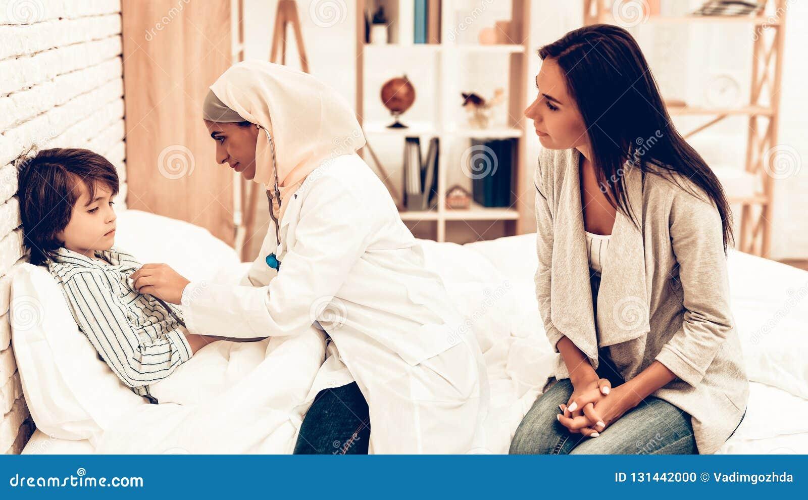 Arabisk kvinnlig pojke för doktor Examining lite