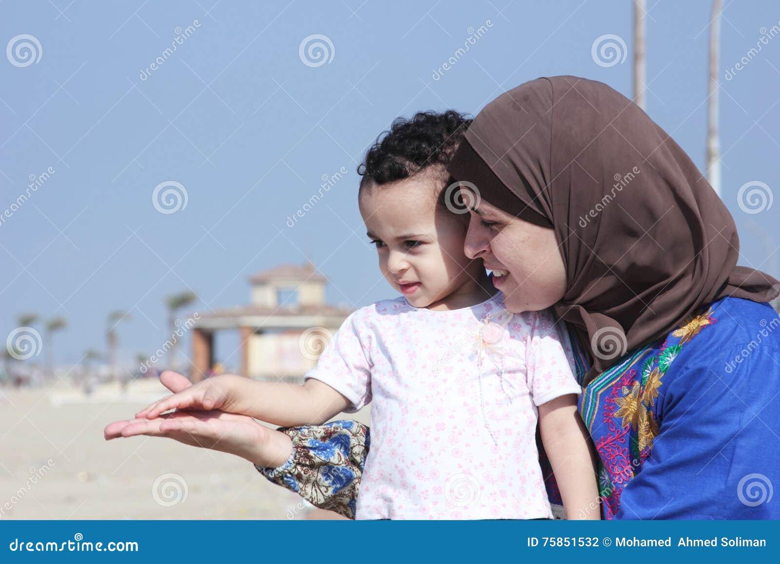 Arabska egipska muzułmańska matka z jej dziewczynką na plaży w Egypt