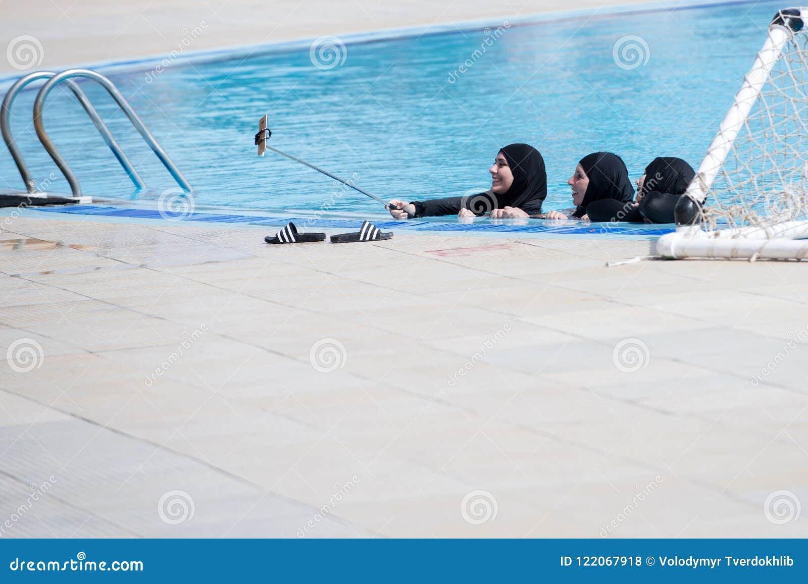 Arabskie kobiety z szczęśliwymi twarzami w czarnym burkini robi selfie