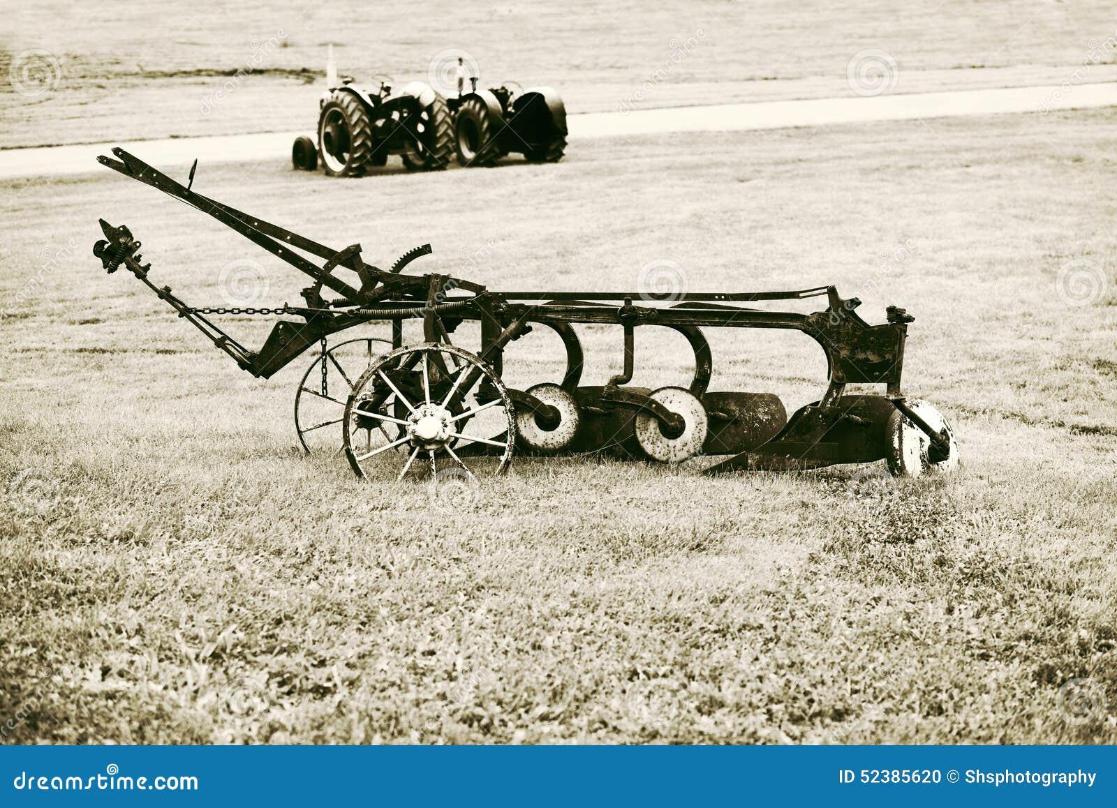 Arado do vintage em um campo de exploração agrícola