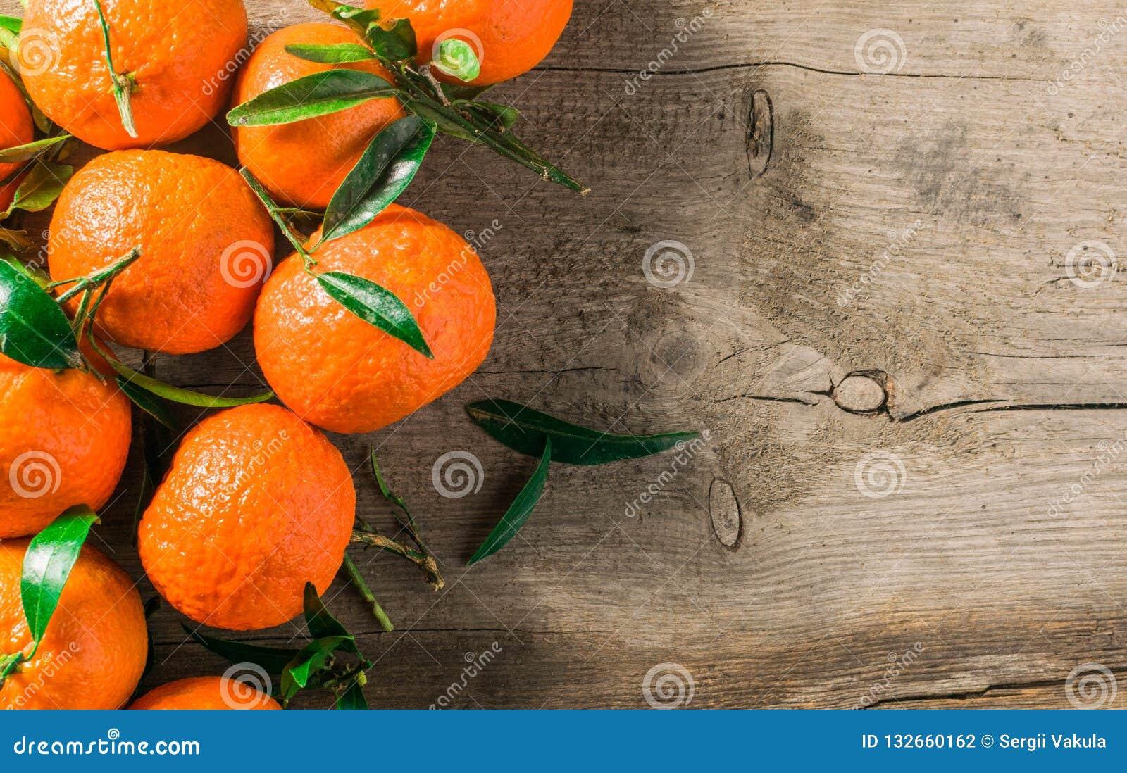 Arance dei mandarini, mandarini, clementine, agrumi con la merce nel carrello delle foglie sopra fondo di legno rustico, spazio d