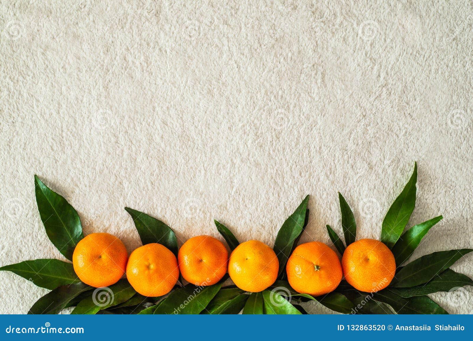 Arance dei mandarini, mandarini, clementine, agrumi con le foglie, fondo, spazio della copia