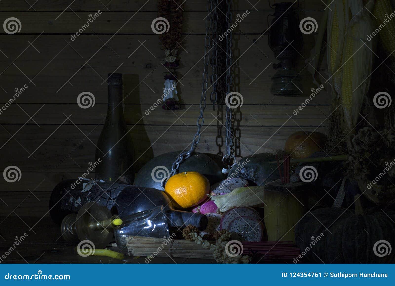 Arance fresche, secche dei frutti, della catena e della bottiglia su legno nella sala