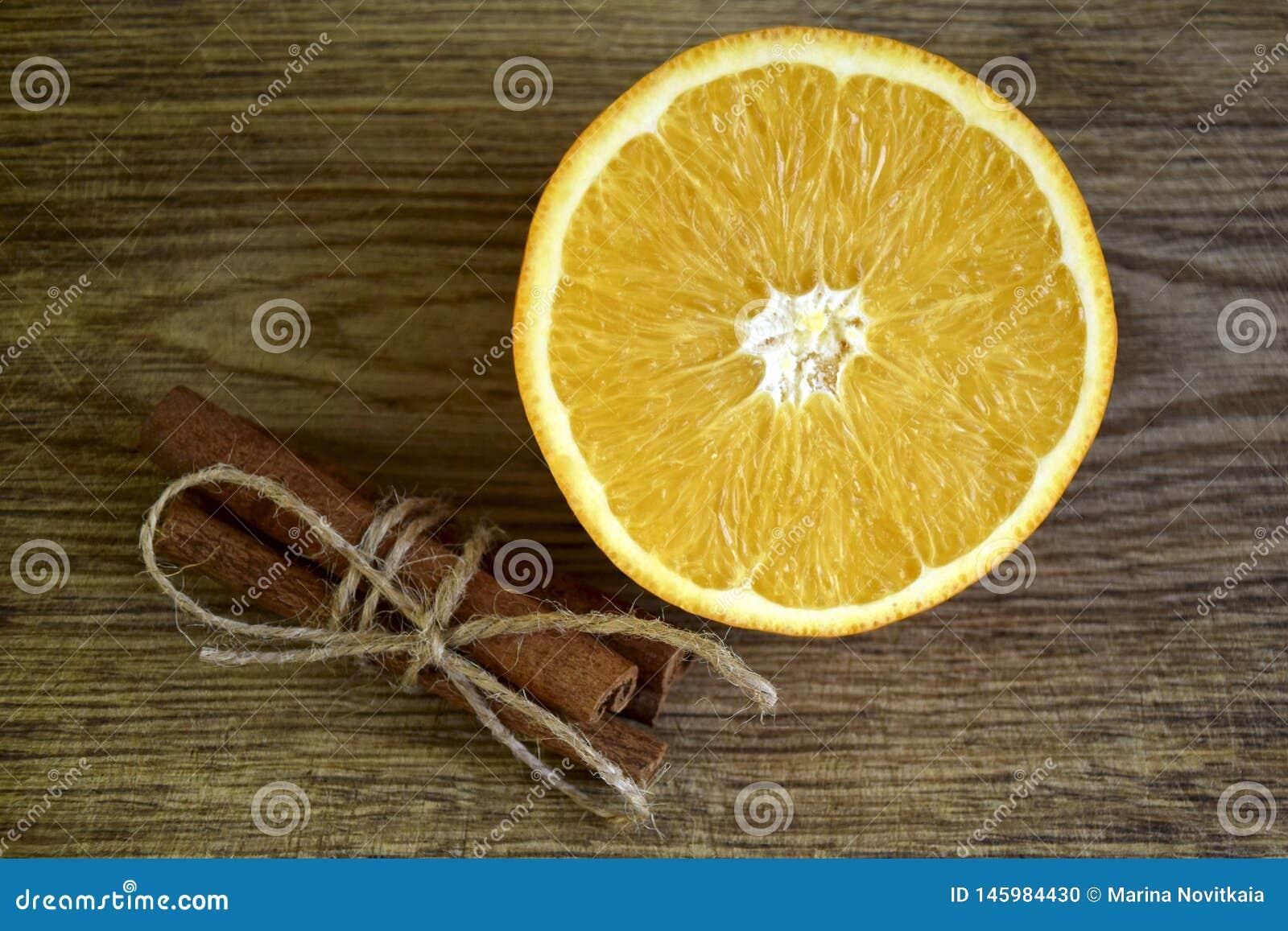 Arancia matura, bastoni di cannella su superficie di legno