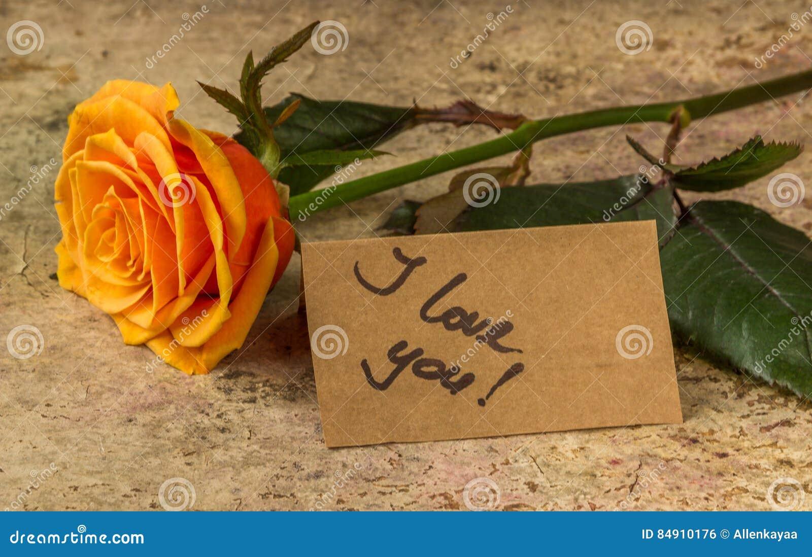 Arancia rosa e nota ti amo sulla carta del mestiere