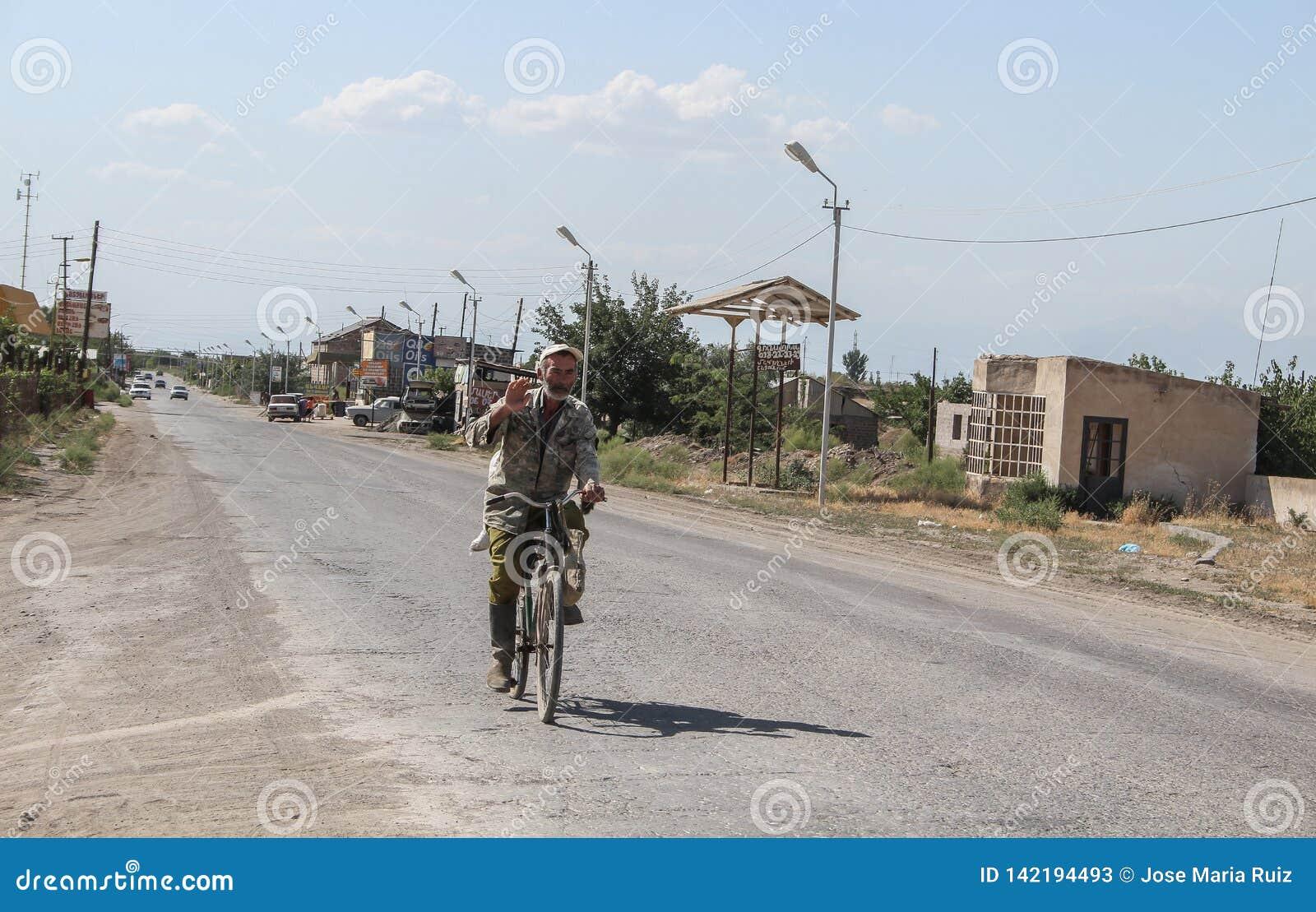 Ararat/Armenia - 07012017: Hombre armenio mayor con el oso blanco en una bici del vintage que envía saludos con la mano