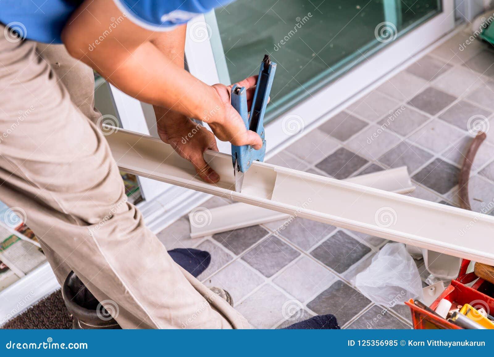 Arbeider die hulpmiddel met behulp van om het plastic pvc-spoor van de pijpkabel te snijden