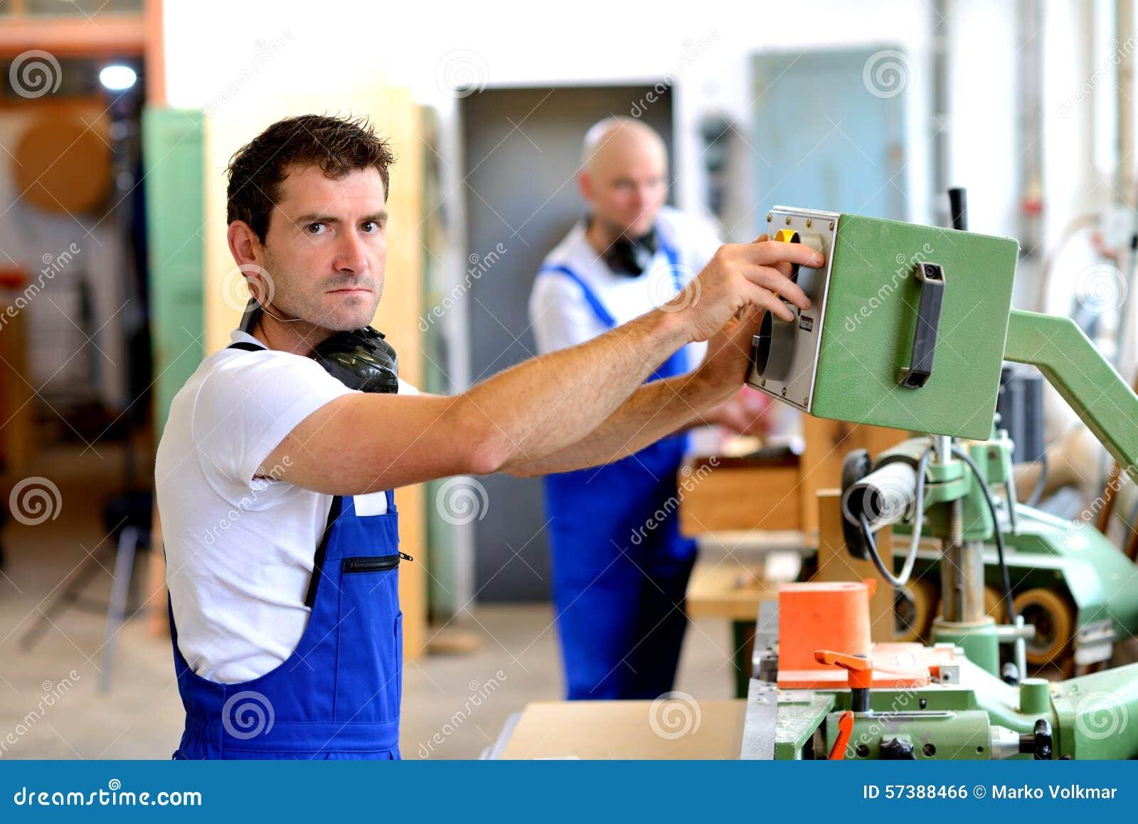 Arbeider in fabriek die machine met behulp van