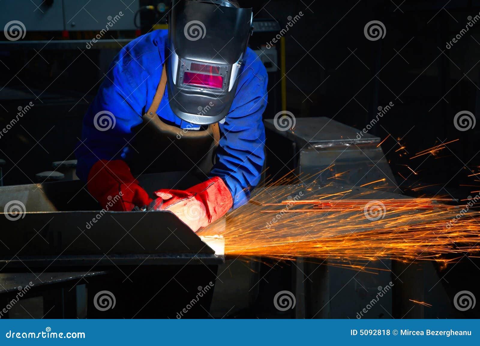 Arbeider met het beschermende masker en handschoenen malen
