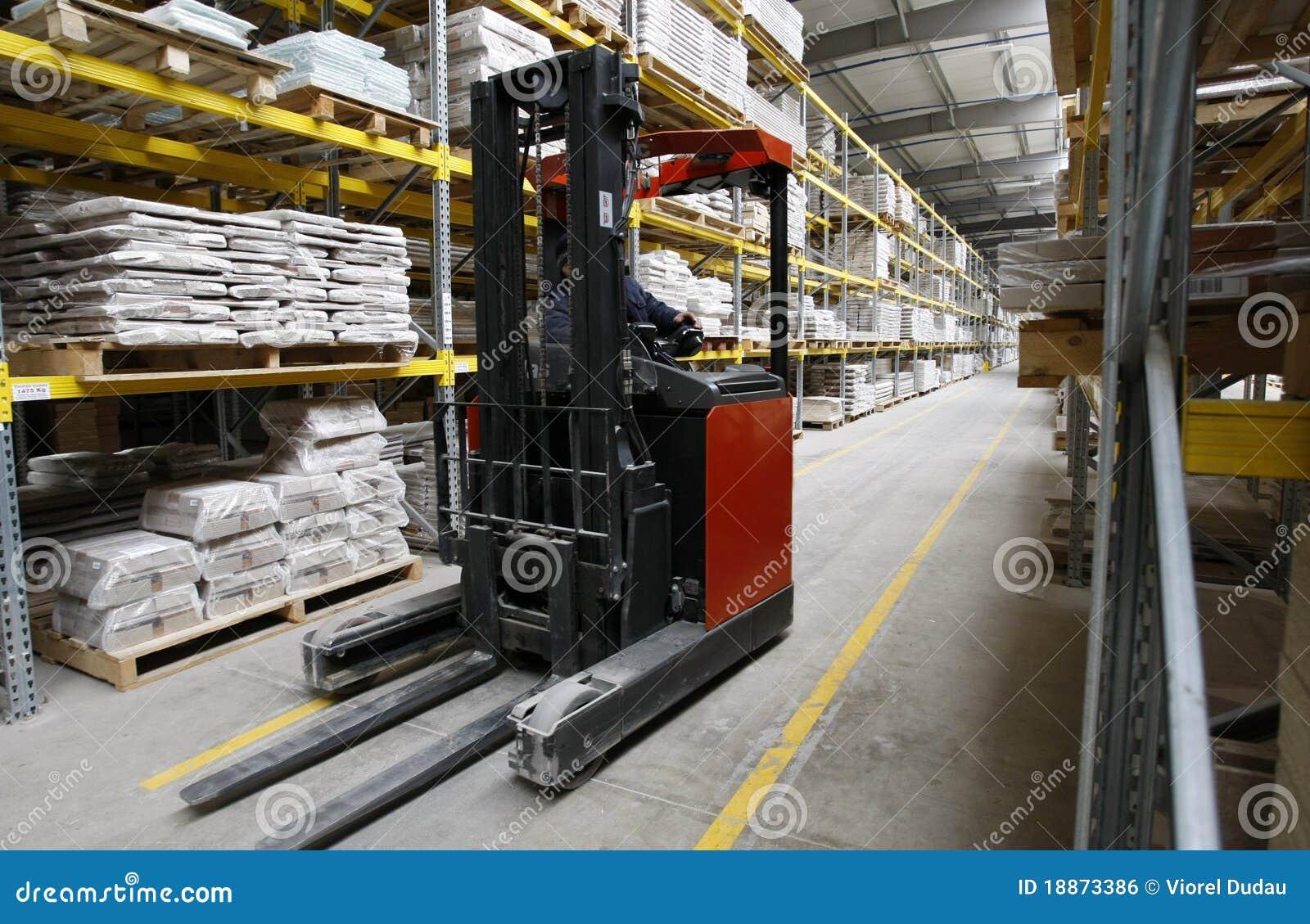 Arbeider met vorkheftruck in houten pakhuis