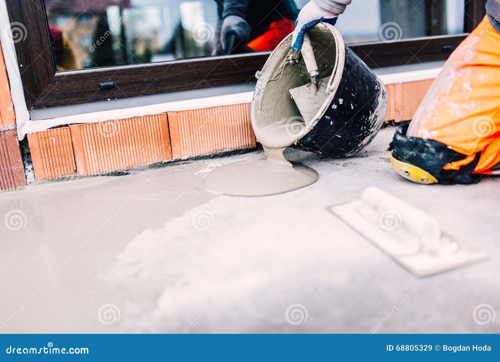 Arbeider op bouwwerf gietend dichtingsproduct van emmer for Huis waterdicht maken