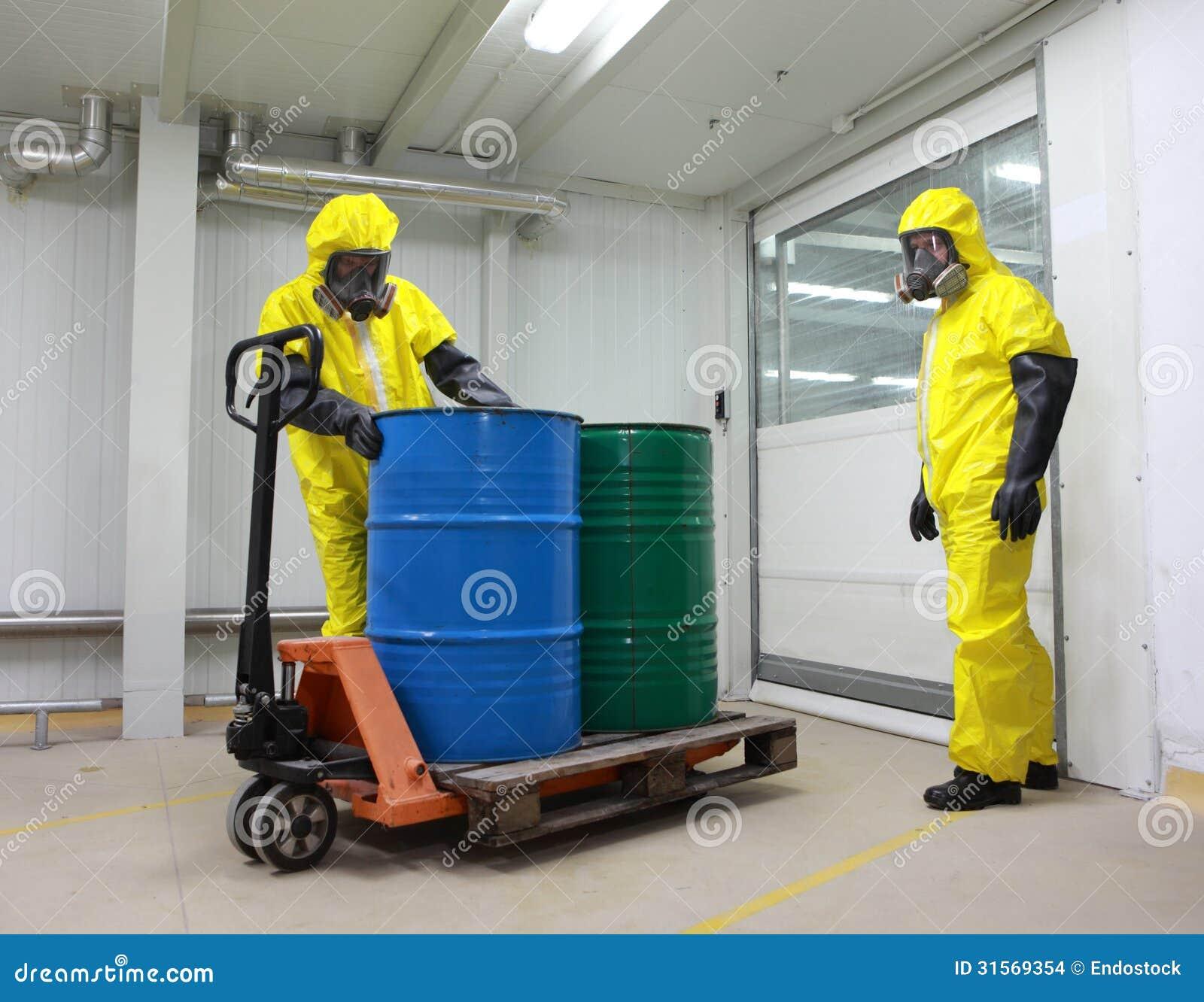 Arbeiders in beschermende uniformen met vaten van giftige substantie