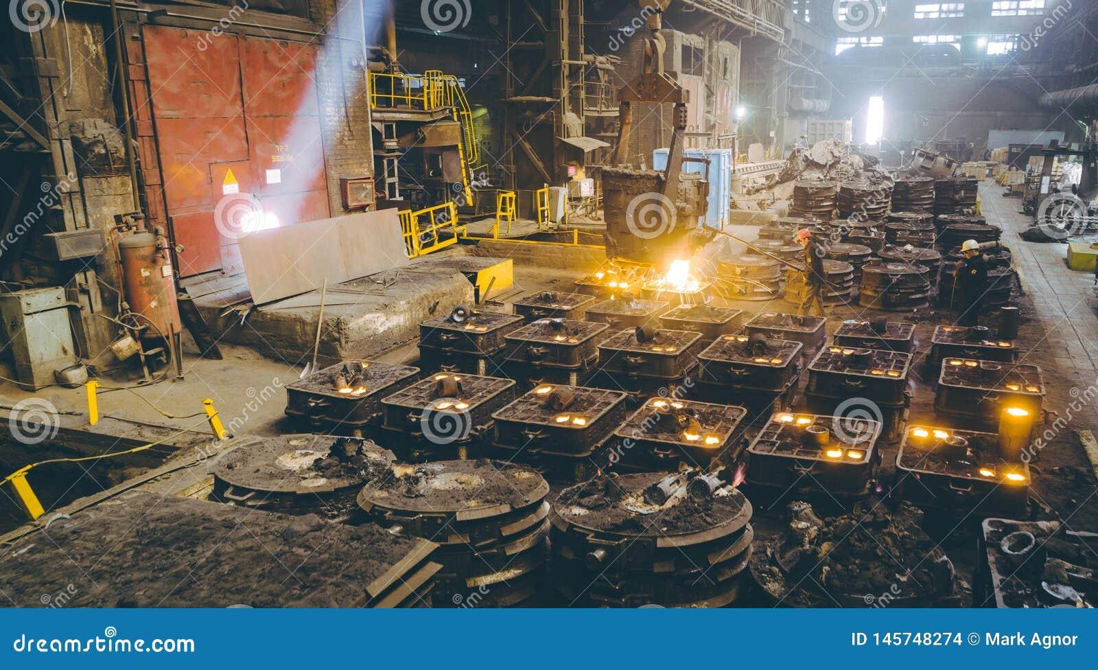 Arbeiders controlerend smelten van metaal in ovens