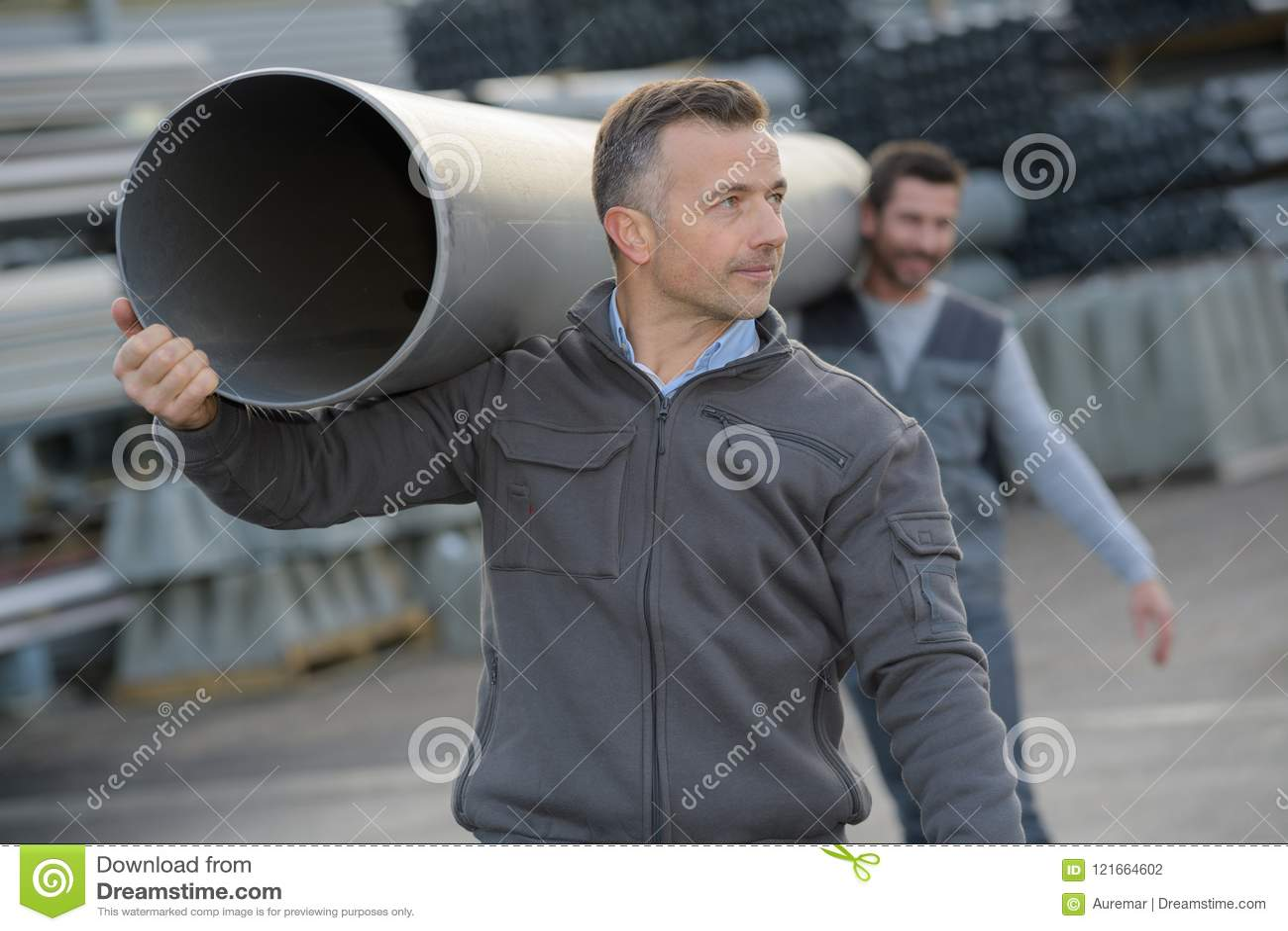 Arbeiders die de rubber flex pijp van buispvc dragen