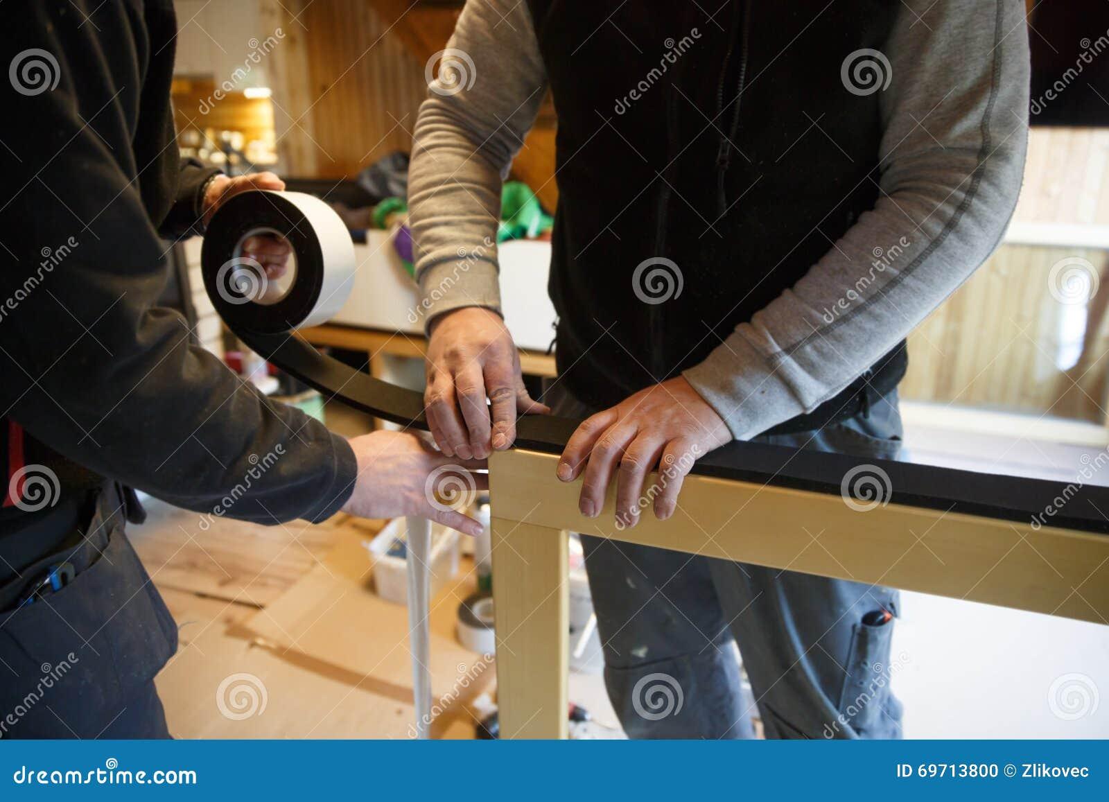 Arbeiders die nieuwe houten vensters voorbereidingen treffen te installeren