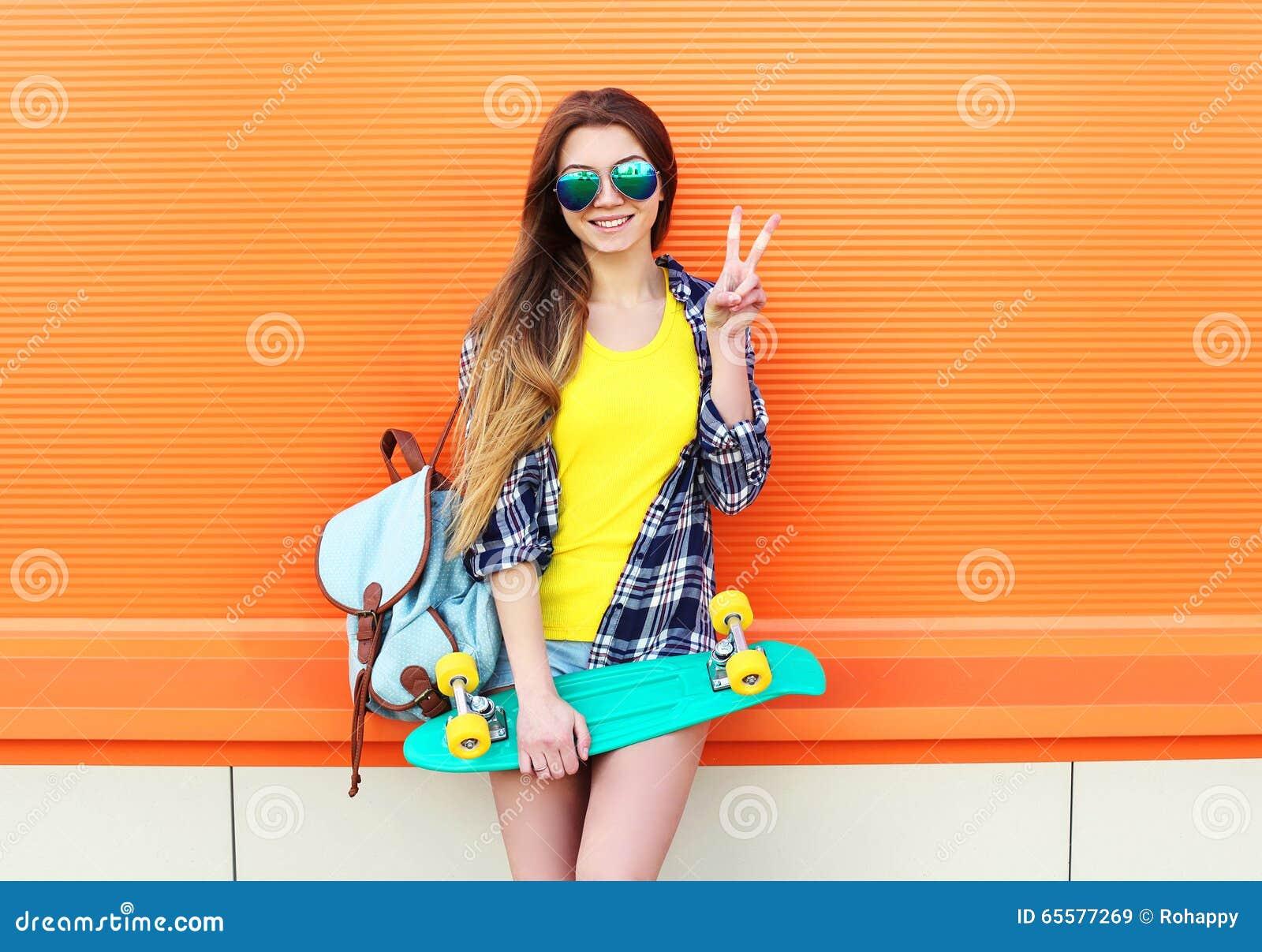 Arbeiten Sie dem recht kühlen Mädchentragen Sonnenbrille, Rucksack mit dem Skateboard um, das Spaß hat