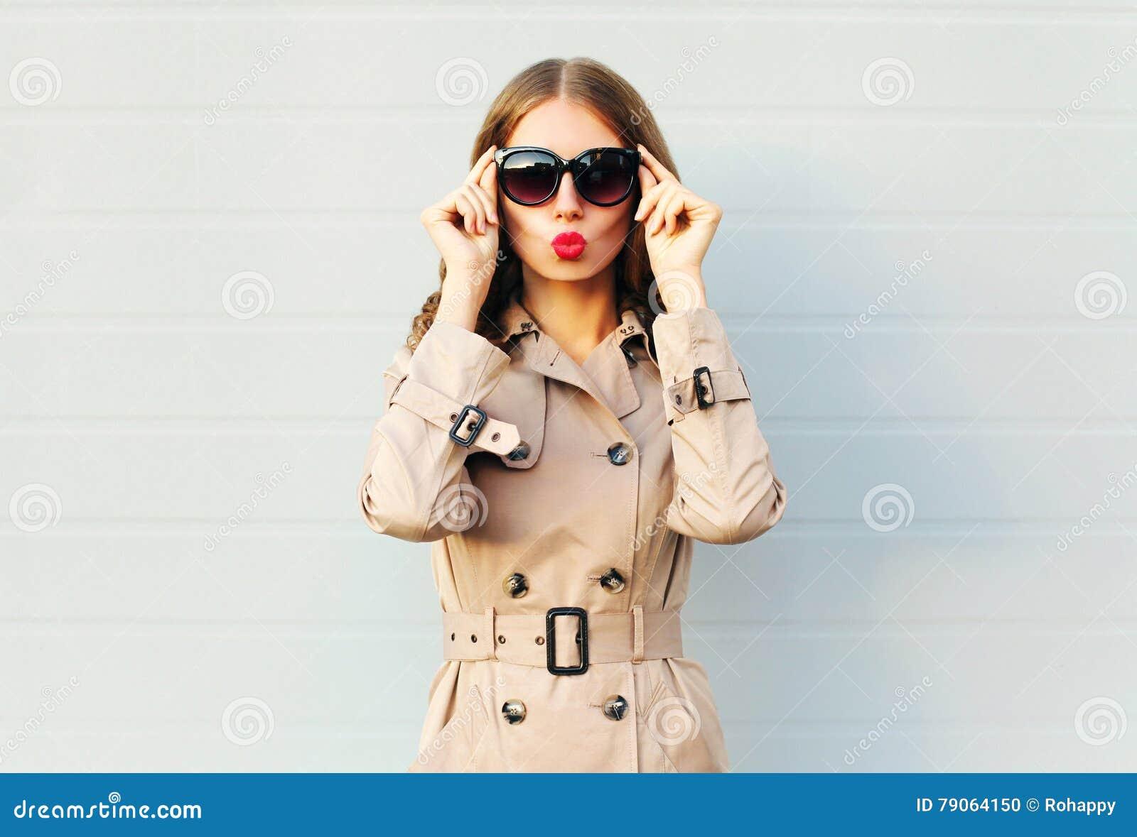 Arbeiten Sie die elegante recht junge Frau um, welche die roten Lippen durchbrennt, die einen schwarzen Sonnenbrillemantel über G