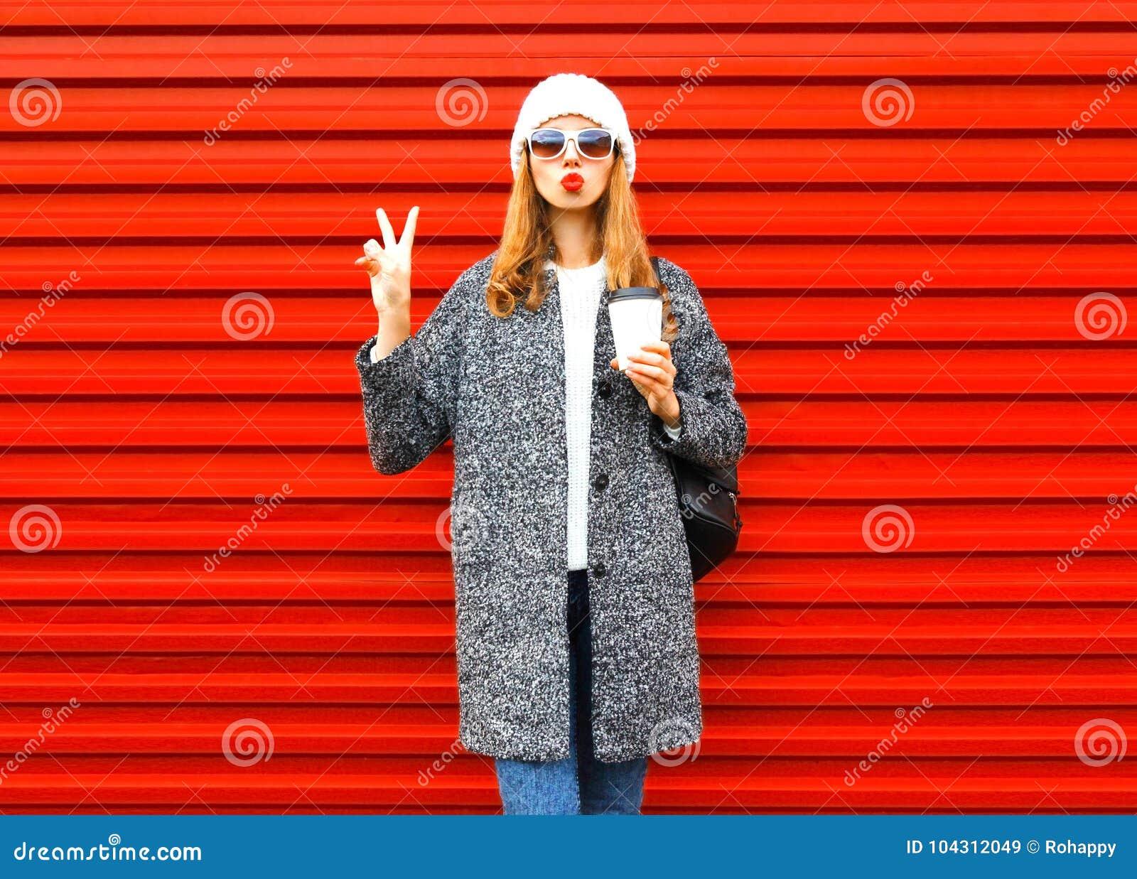 Arbeiten Sie hübsche Frau mit Kaffeetasse im Mantel um, der auf Rot aufwirft