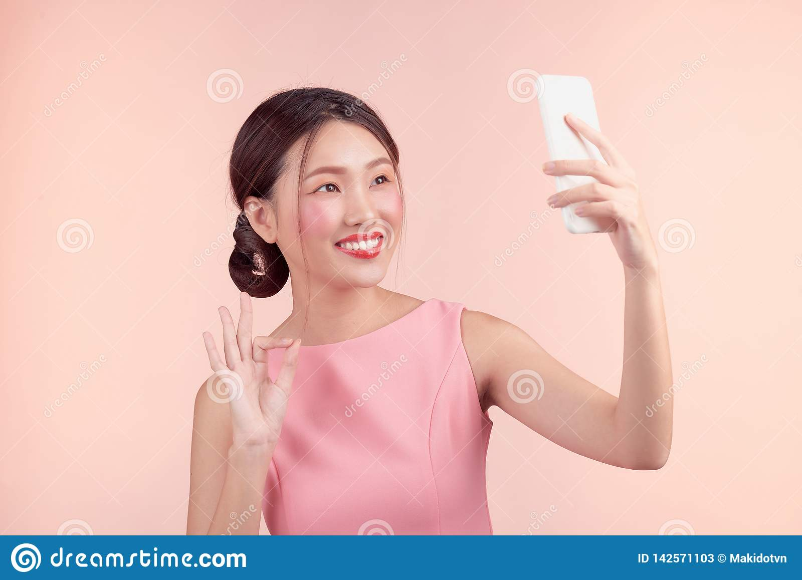 Arbeiten Sie Porträt einer schönen jungen Frau in einem hübschen Kleid über rosa Hintergrund um