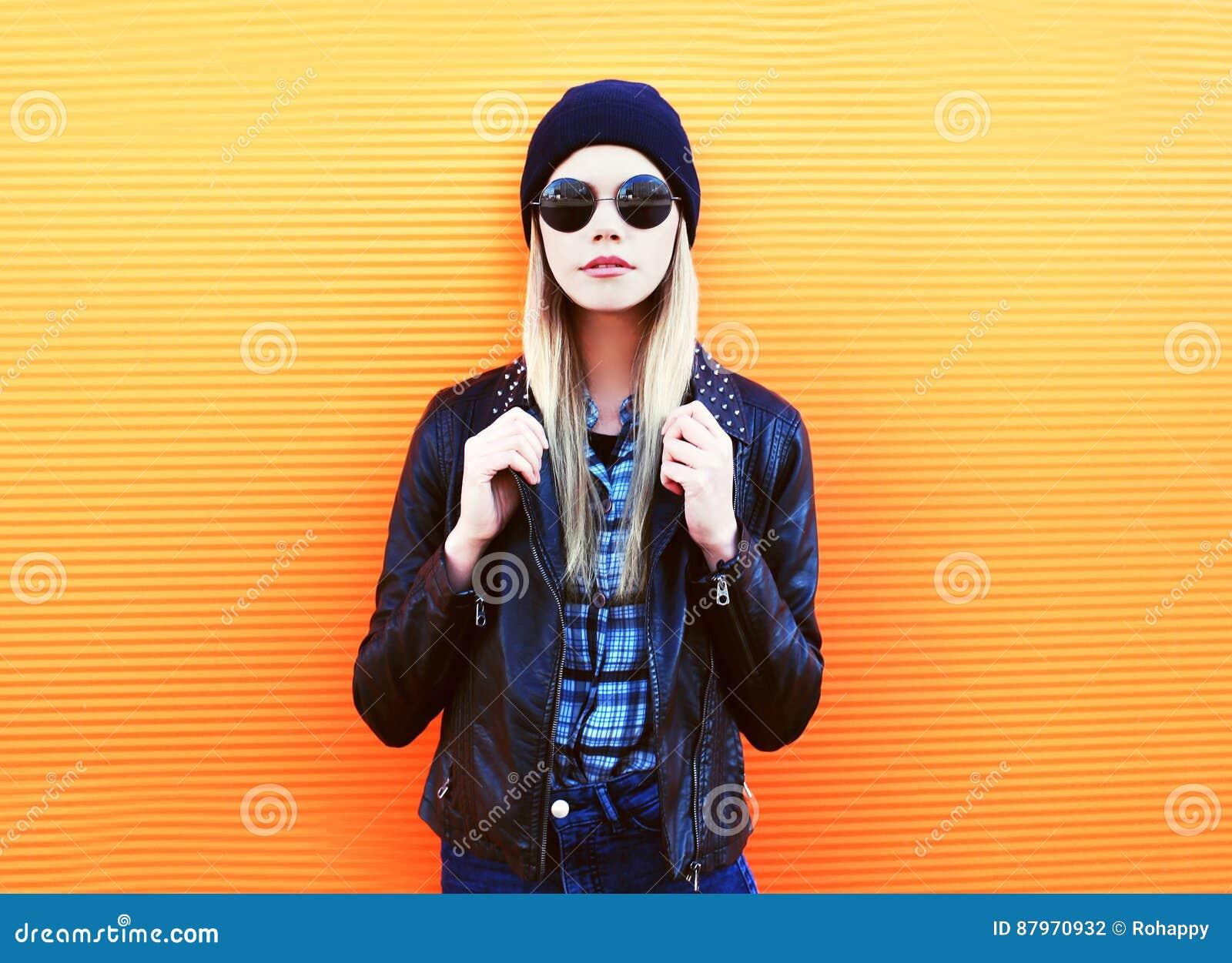 Arbeiten Sie Porträt hübsche Blondine in der Felsenschwarzart auf einem bunten orange Hintergrund um