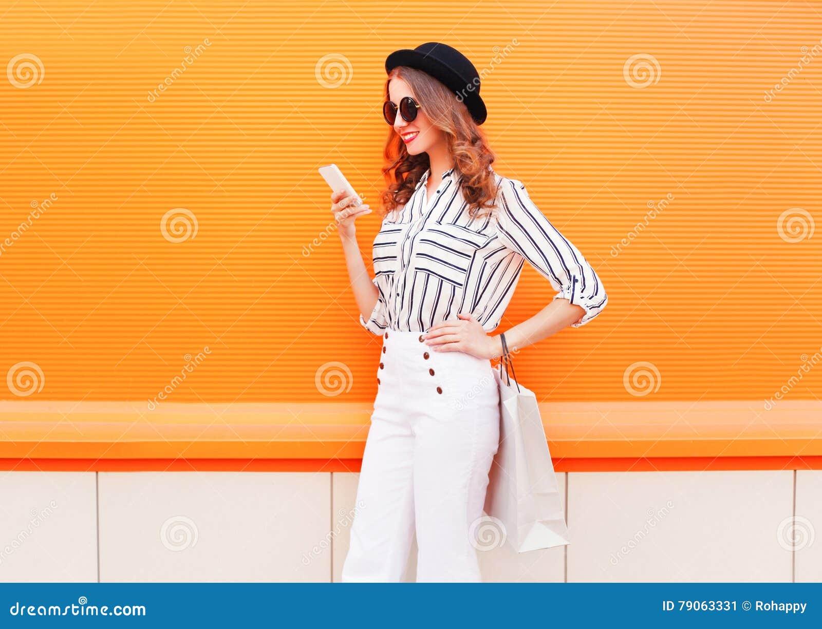 Arbeiten Sie recht glückliches junges lächelndes Frauenmodell unter Verwendung des Smartphone mit den Einkaufstaschen um, die wei
