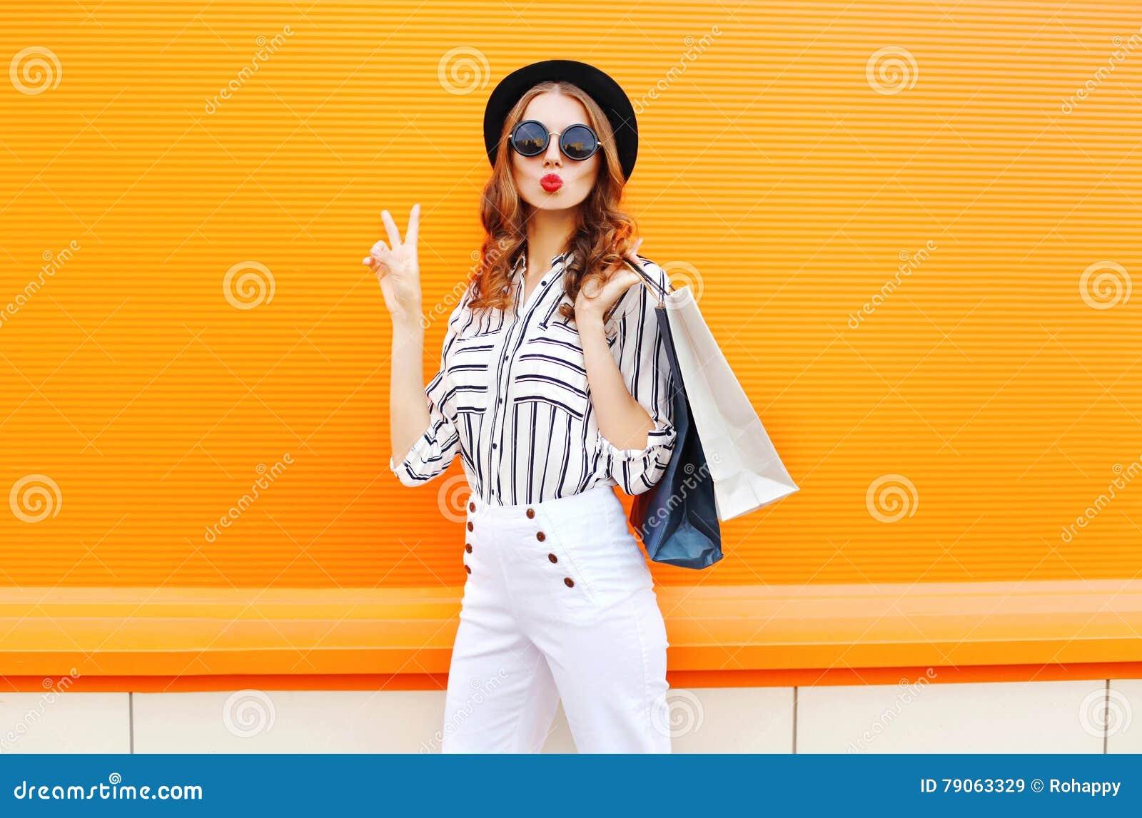 Arbeiten Sie recht kühles junges Mädchen mit den Einkaufstaschen um, die weiße Hosen eines schwarzen Hutes über bunter Orange tra