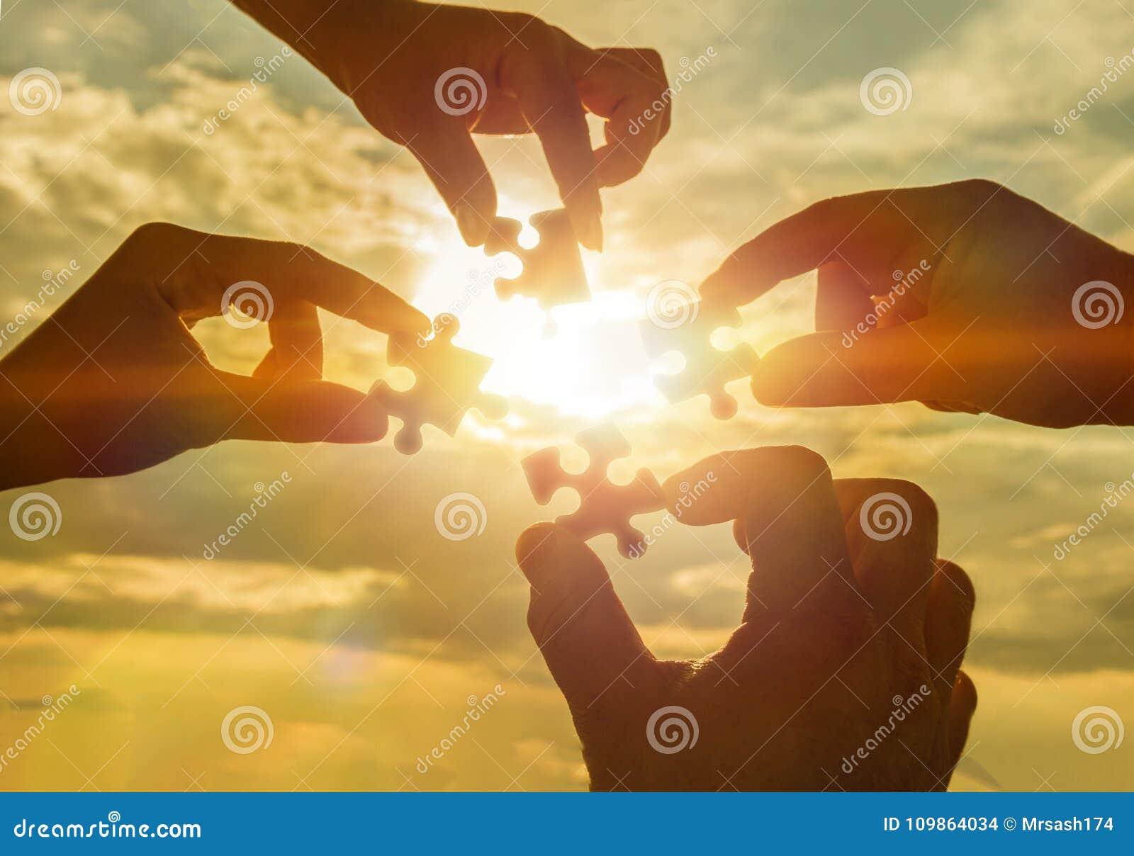 Arbeiten vier Hände zusammen, die versuchen, ein Puzzlespielstück mit einem Sonnenunterganghintergrund anzuschließen