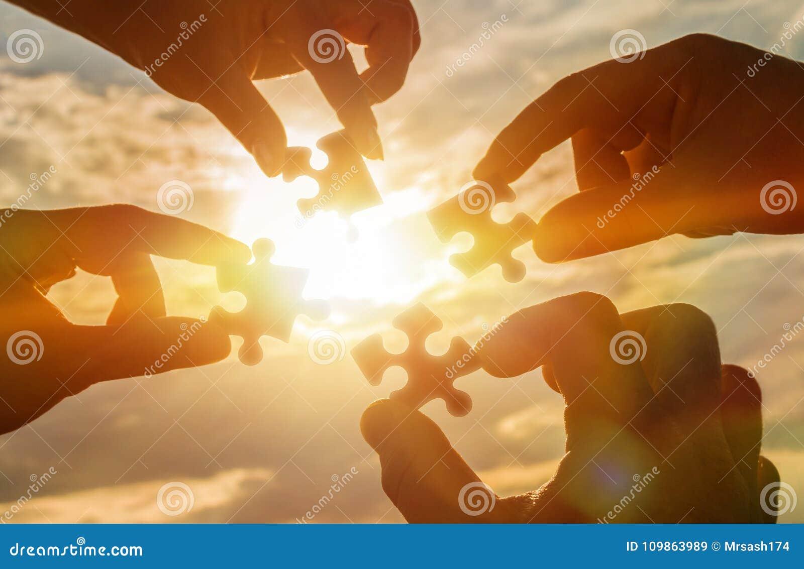Arbeiten vier Hände zusammen, die versuchen, ein Puzzlespielstück mit einem Sonnenunterganghintergrund anzuschließen Ein Puzzlesp