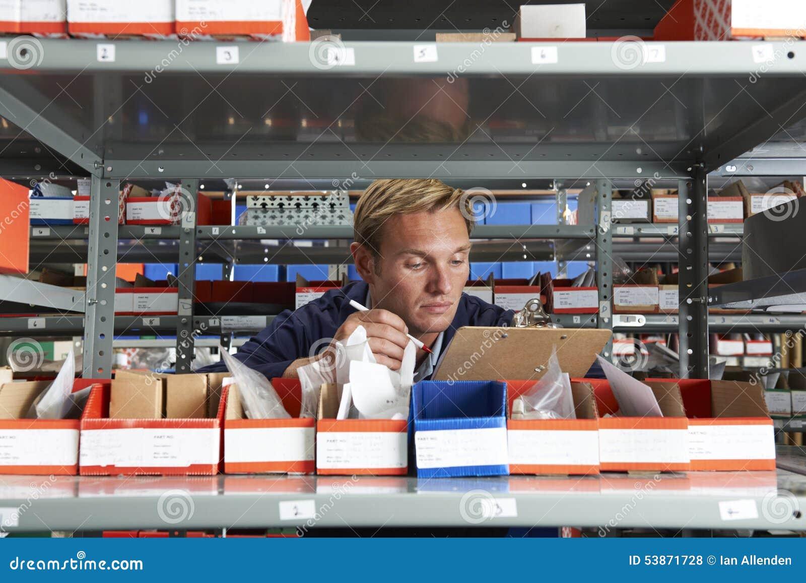 Arbeiter In Store Room, das Vorrat überprüft