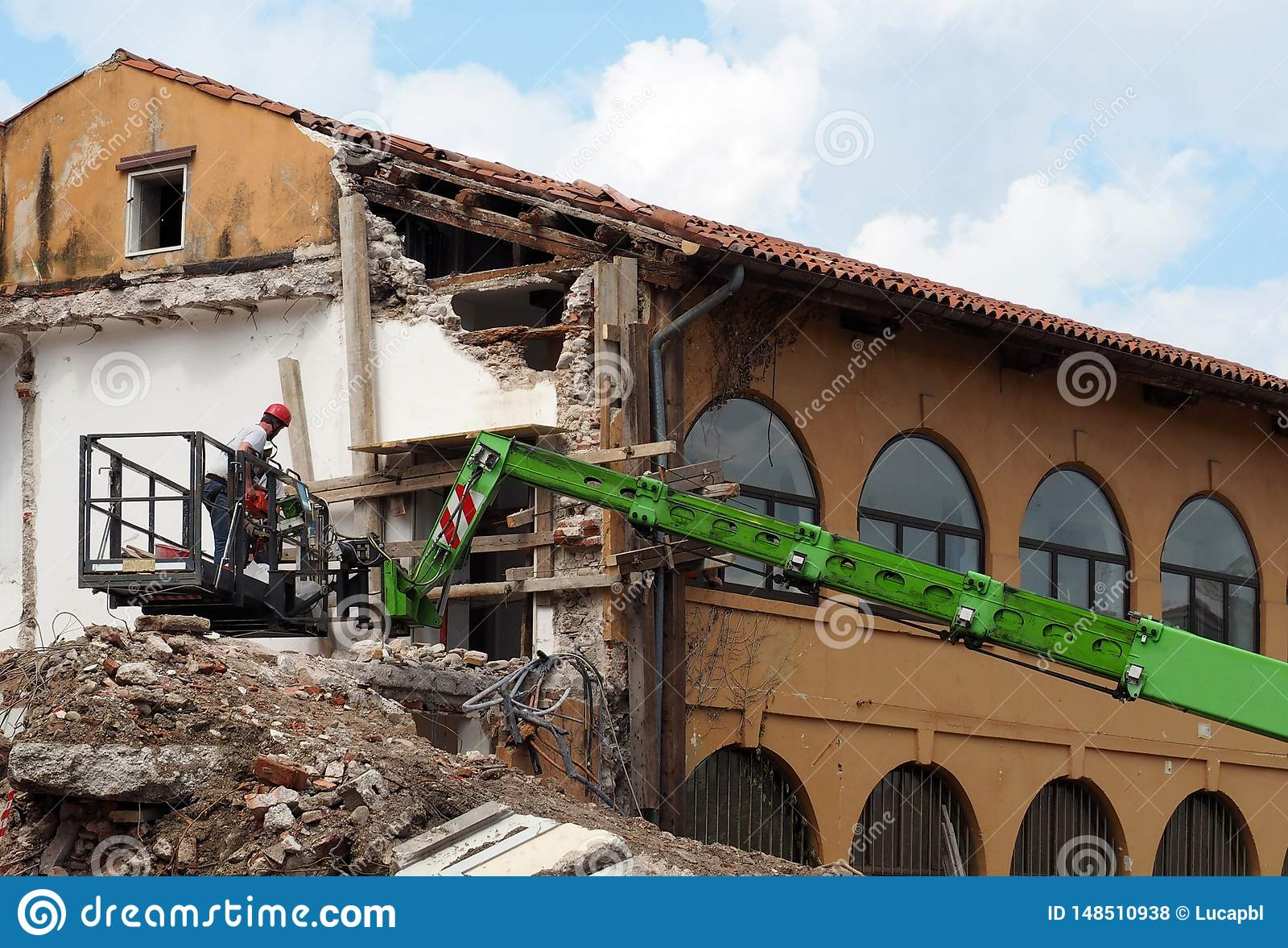 Arbeitskräfte auf einem Kirschpflücker bei der Arbeit während der Erneuerung eines teilweise demolierten Gebäudes