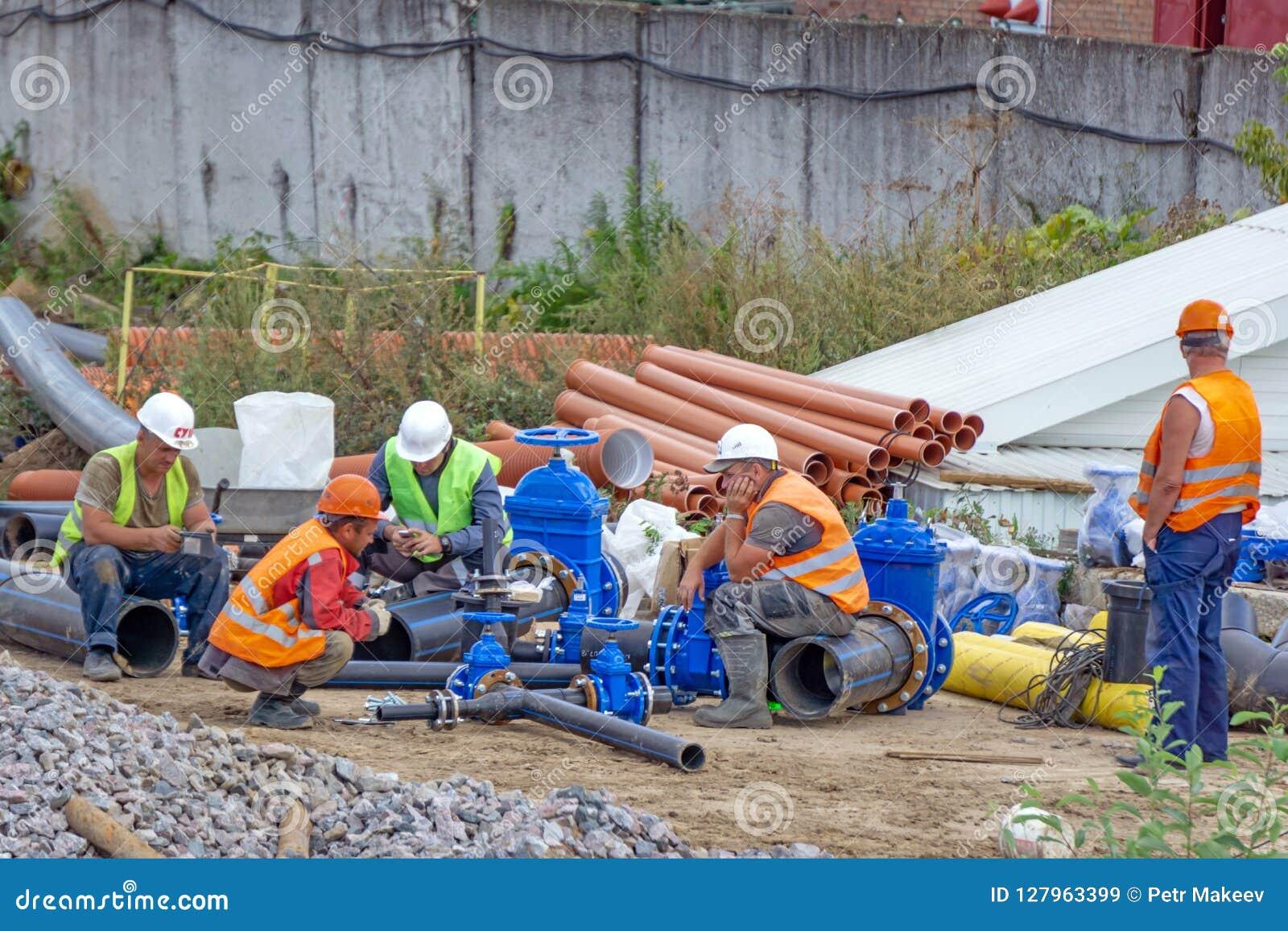 Arbeitskräfte am Bruch und sammeln Rohrleitung
