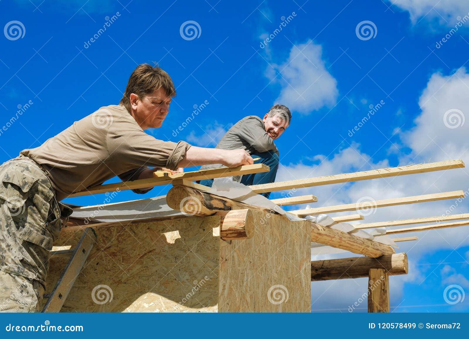 Arbeitskräfte stellen ein Dach in einem Landhaus her