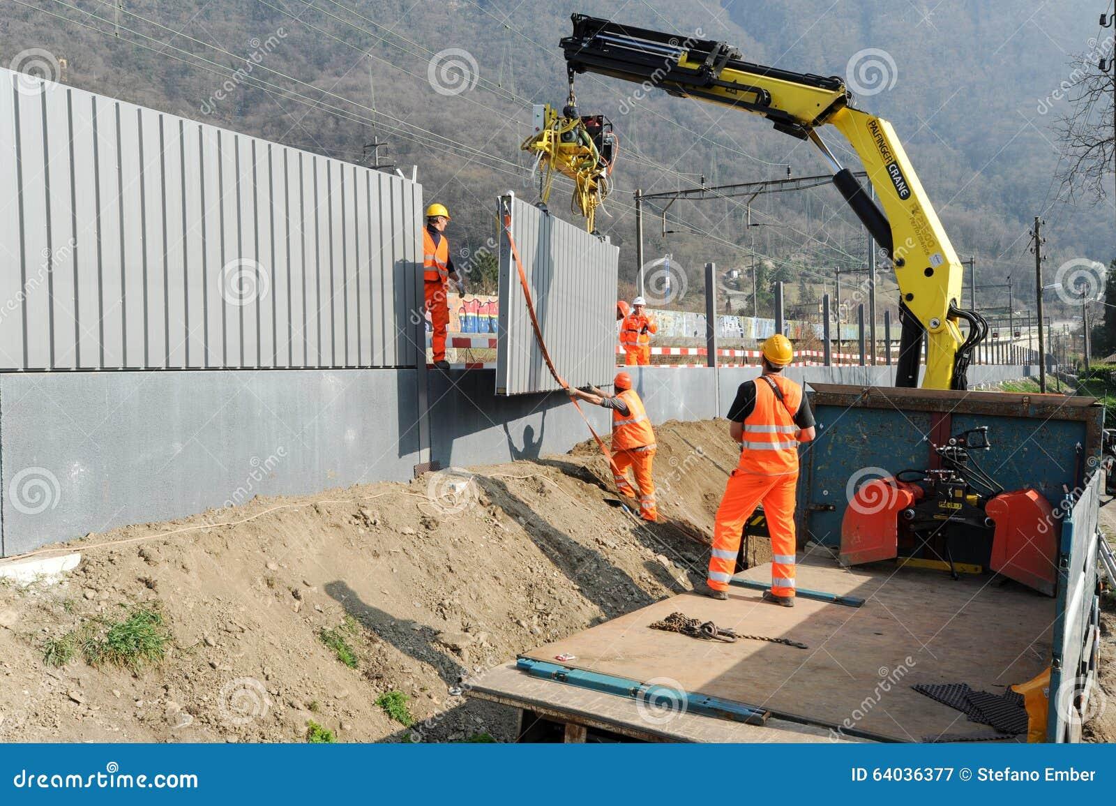 Arbeitskräfte während der Installation der Geräuschsperren auf der Eisenbahn