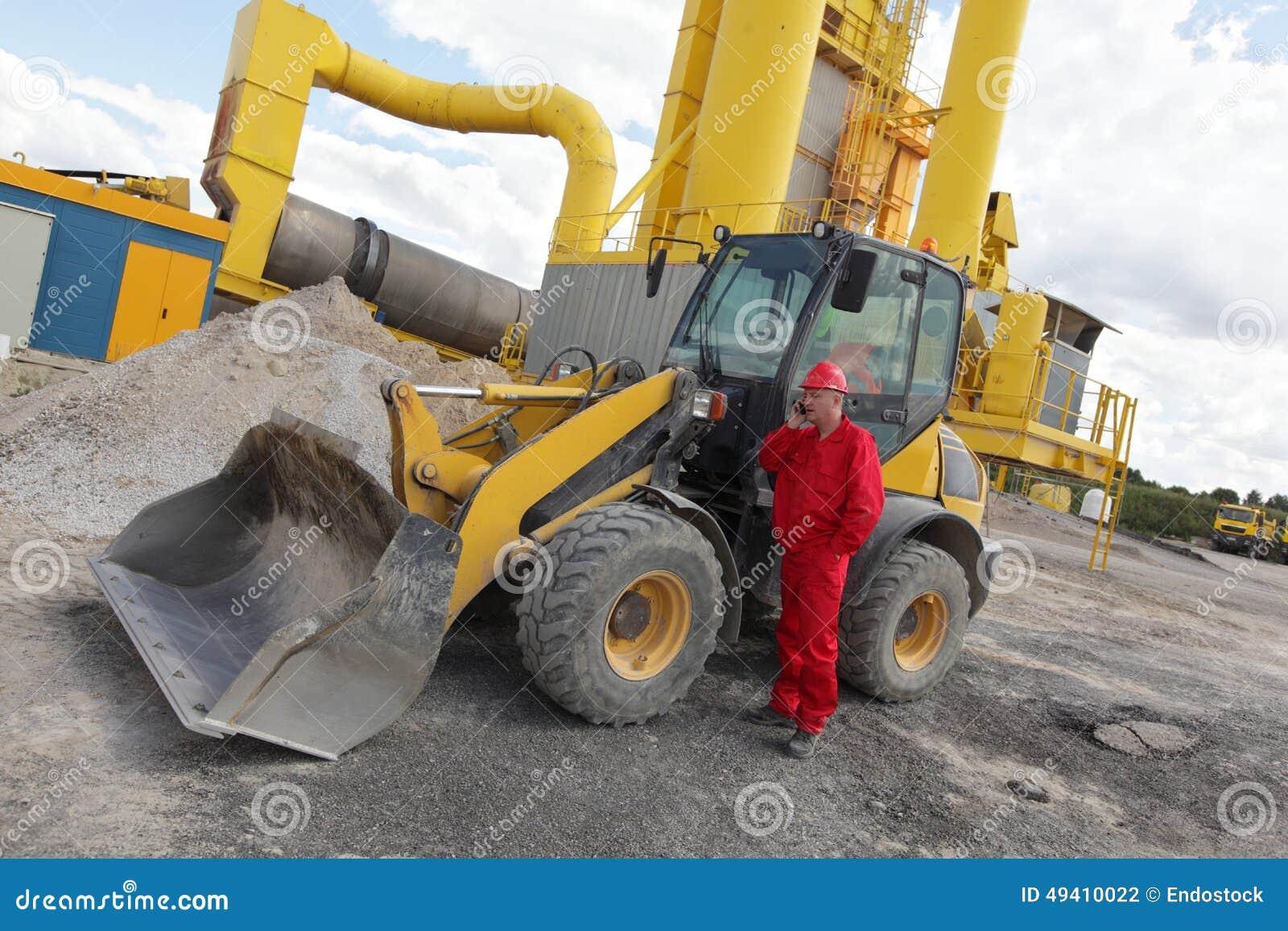 Download Arbeitskraft In Der Roten Uniform Am Telefon Am Buldozer An Der Baustelle Stockfoto - Bild von schwer, coveralls: 49410022