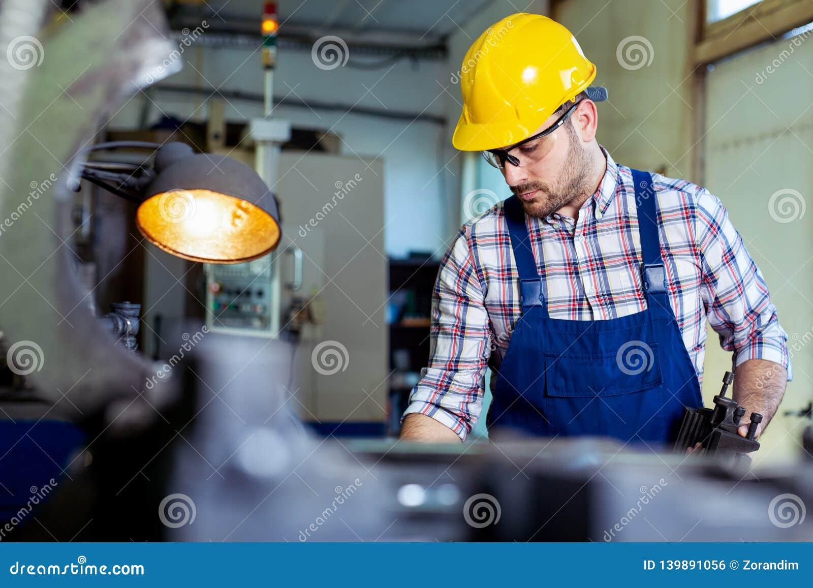 Arbeitskraft in der Uniform, die in der manuellen Drehbank in der Metallindustriefabrik funktioniert