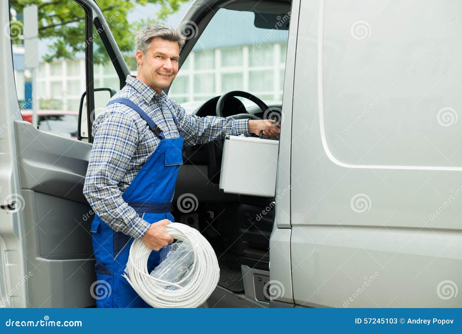 Arbeitskraft mit dem Werkzeugkasten und Kabel, die in Van hereinkommen