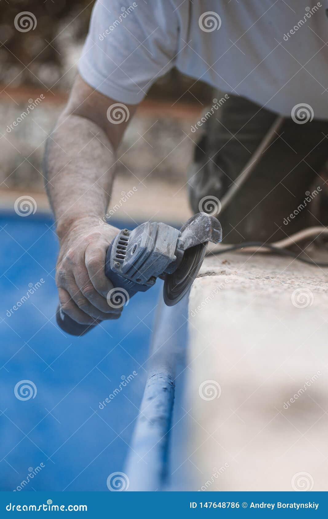 Arbeitskraft mit Radialstrahl sah mit Staub auf der Luft mit blauem Hintergrund