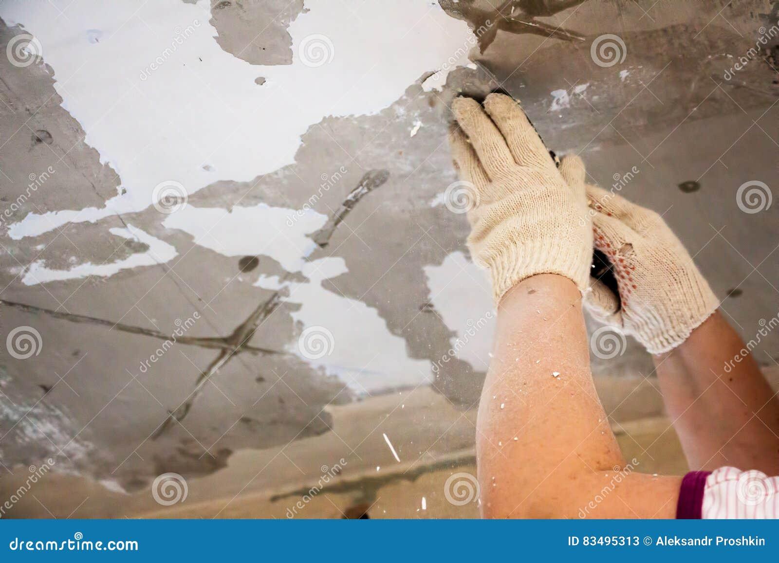 Arbeitskraft reibt die alte Farbe