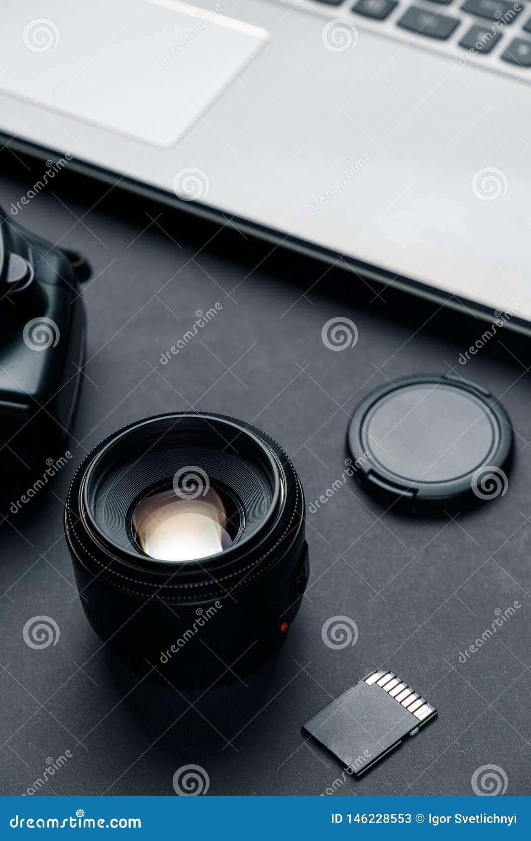 Arbeitsplatz auf schwarzer Tabelle des Fotografen Minimaler Arbeitsplatz mit Laptop