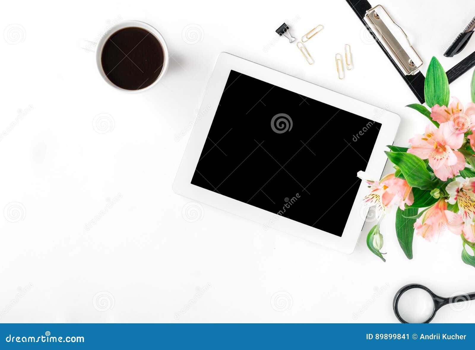 Arbeitsplatz mit Tablette, Bürozubehör, Kaffee und Blumenstrauß von