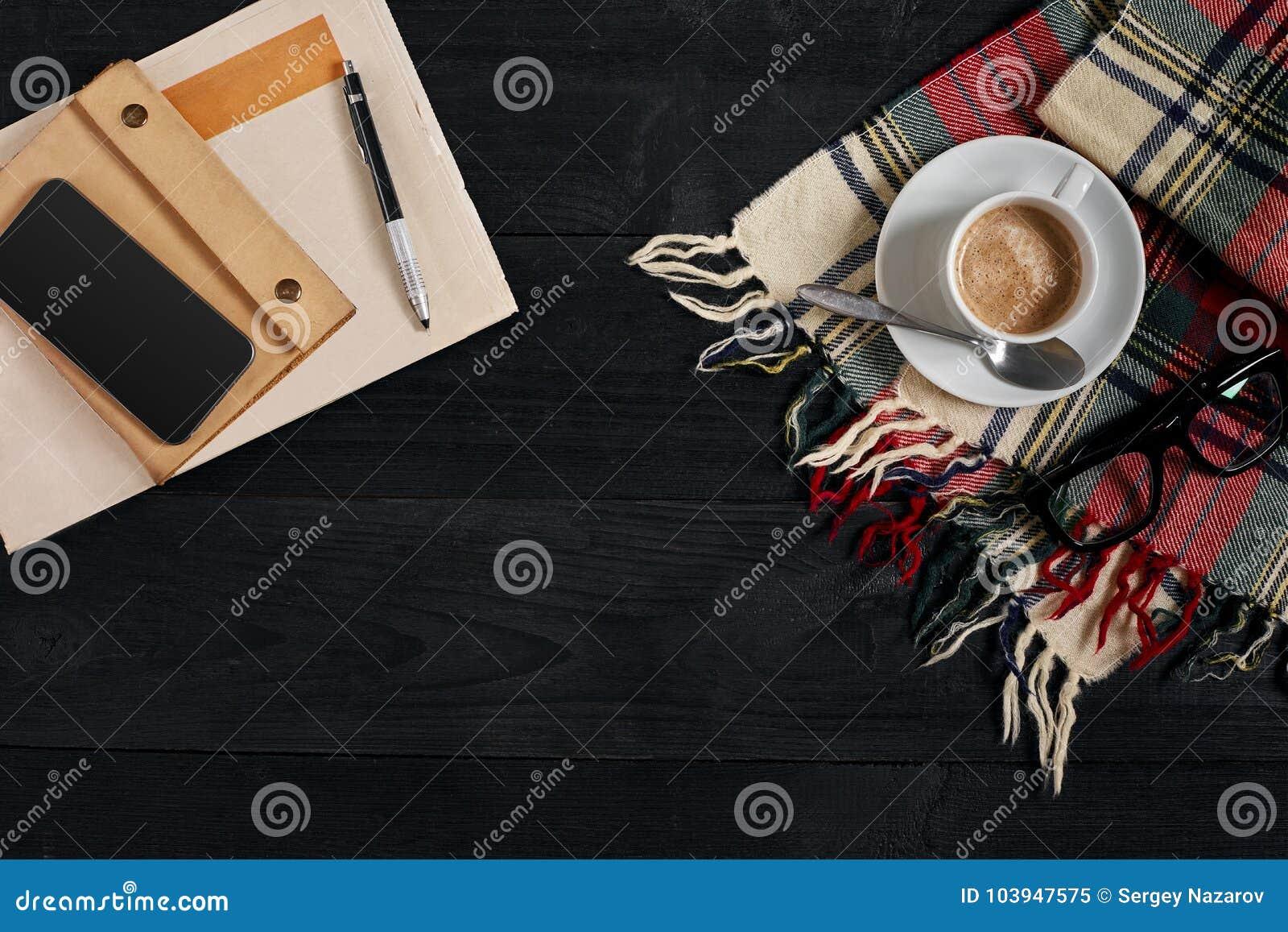 Arbeitsplatz mit Zeitung, Kaffeetasse, Schal, Gläser Stilvoller Schreibtisch Herbst- oder Winterkonzept Flache Lage, Draufsicht