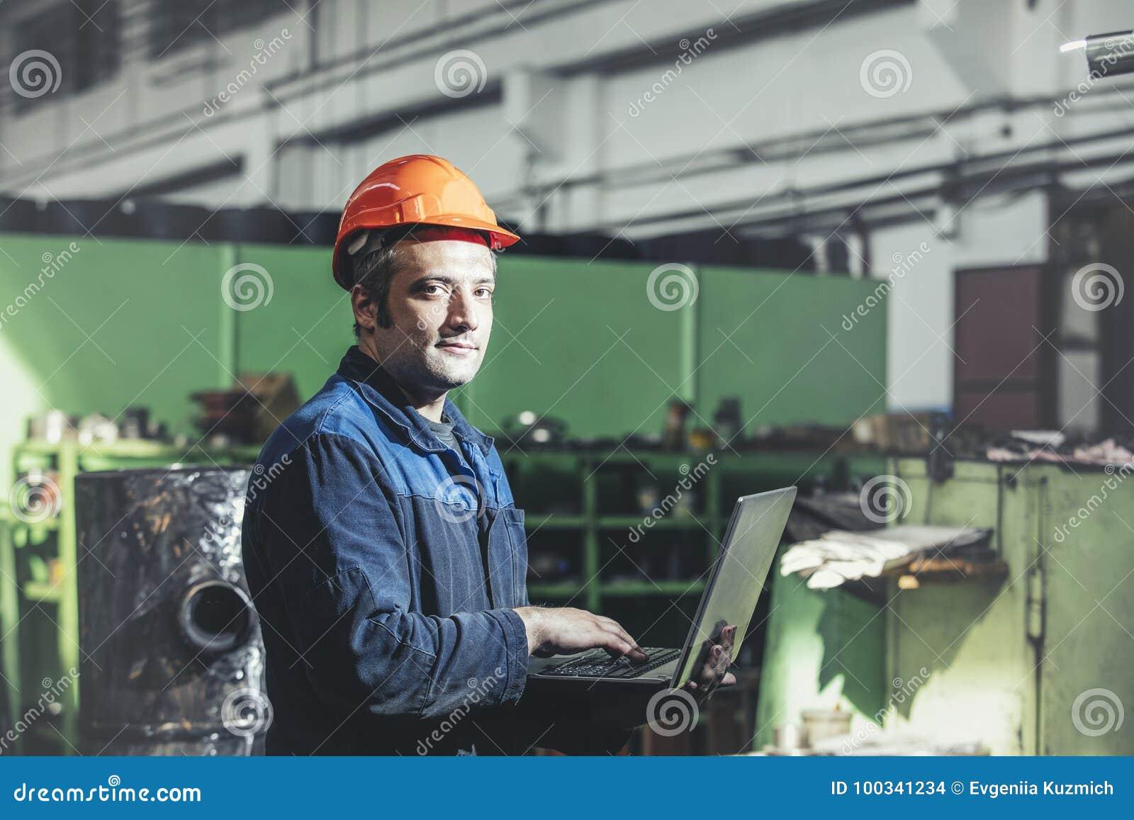 Arbeta i växten med en bärbar dator i hand på bakgrunden av