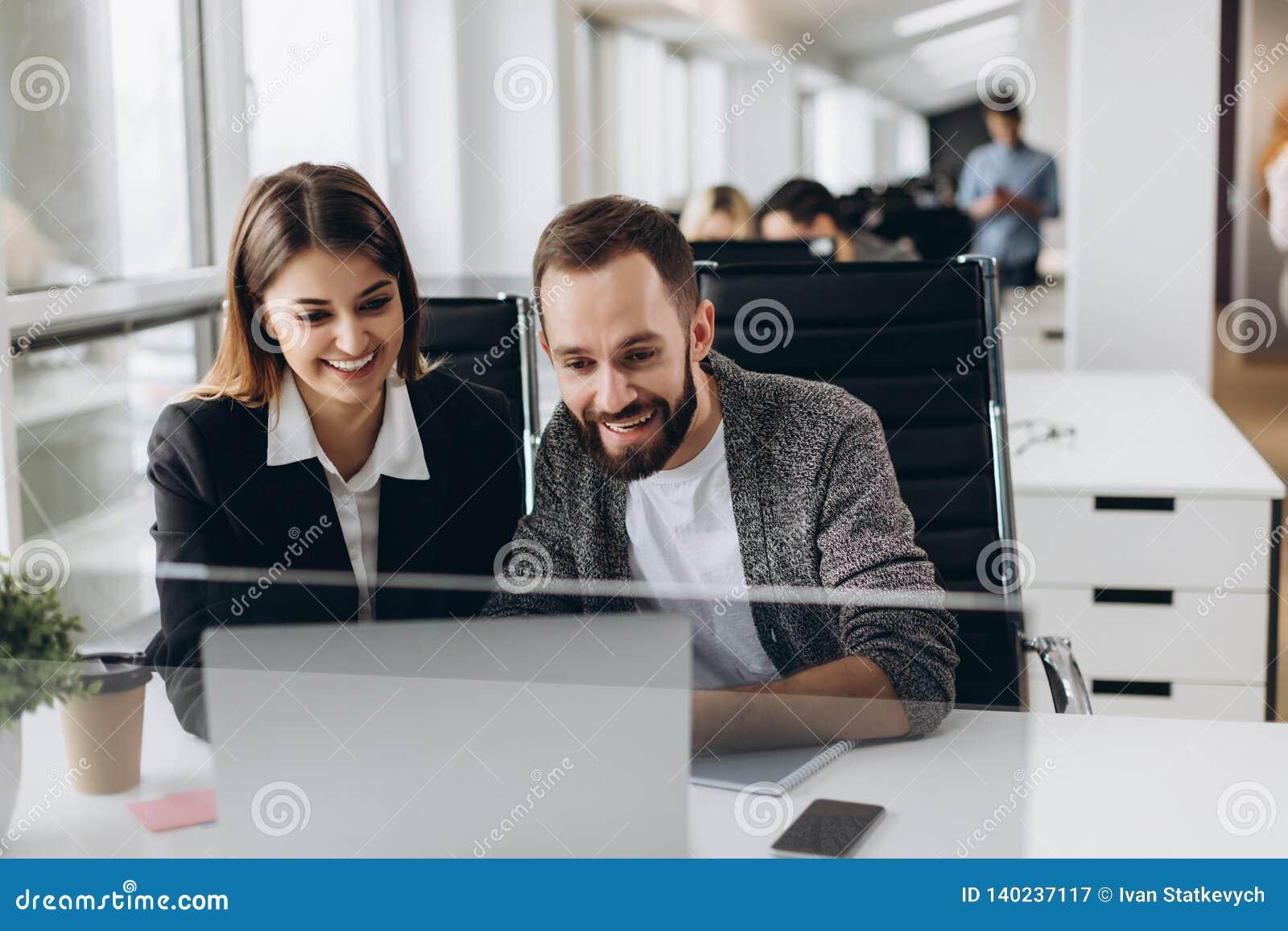 Arbeta tillsammans på projekt Två unga affärskollegor som arbetar på datoren