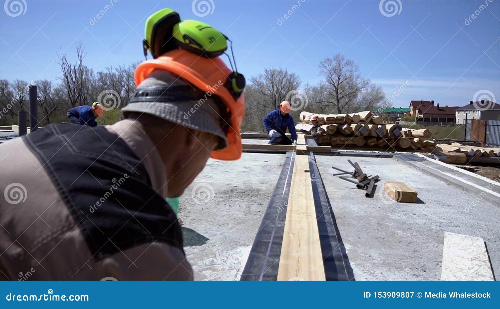 Arbetare av att mäta träbräden på konstruktionsplatsen gem Byggmästare gör mätningar av bräden för konstruktion av