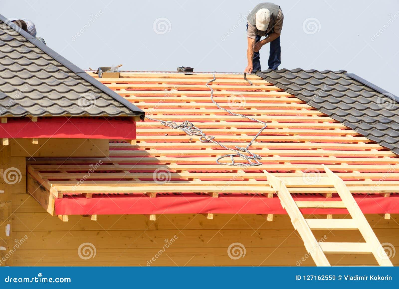 Arbetare bygger ett tak på huset