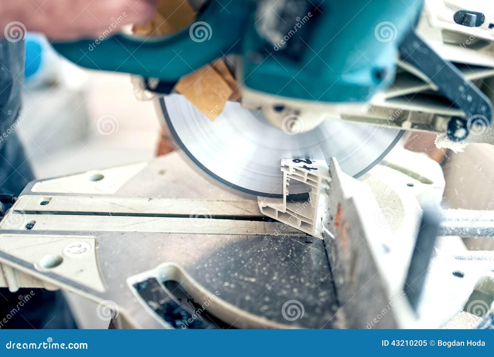 Arbetare eller faktotum som klipper PVC-profil med cirkelsågen
